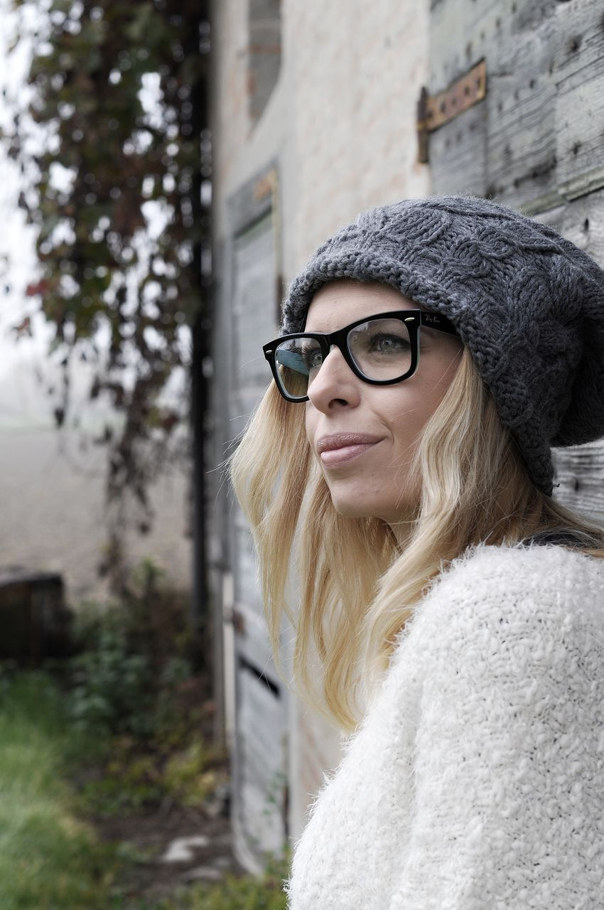 eyeglasses, young adult, real people, young women, one person, lifestyles, architecture, leisure activity, outdoors, looking at camera, building exterior, front view, built structure, day, portrait, glasses, beautiful woman, smiling, happiness, warm clothing, close-up