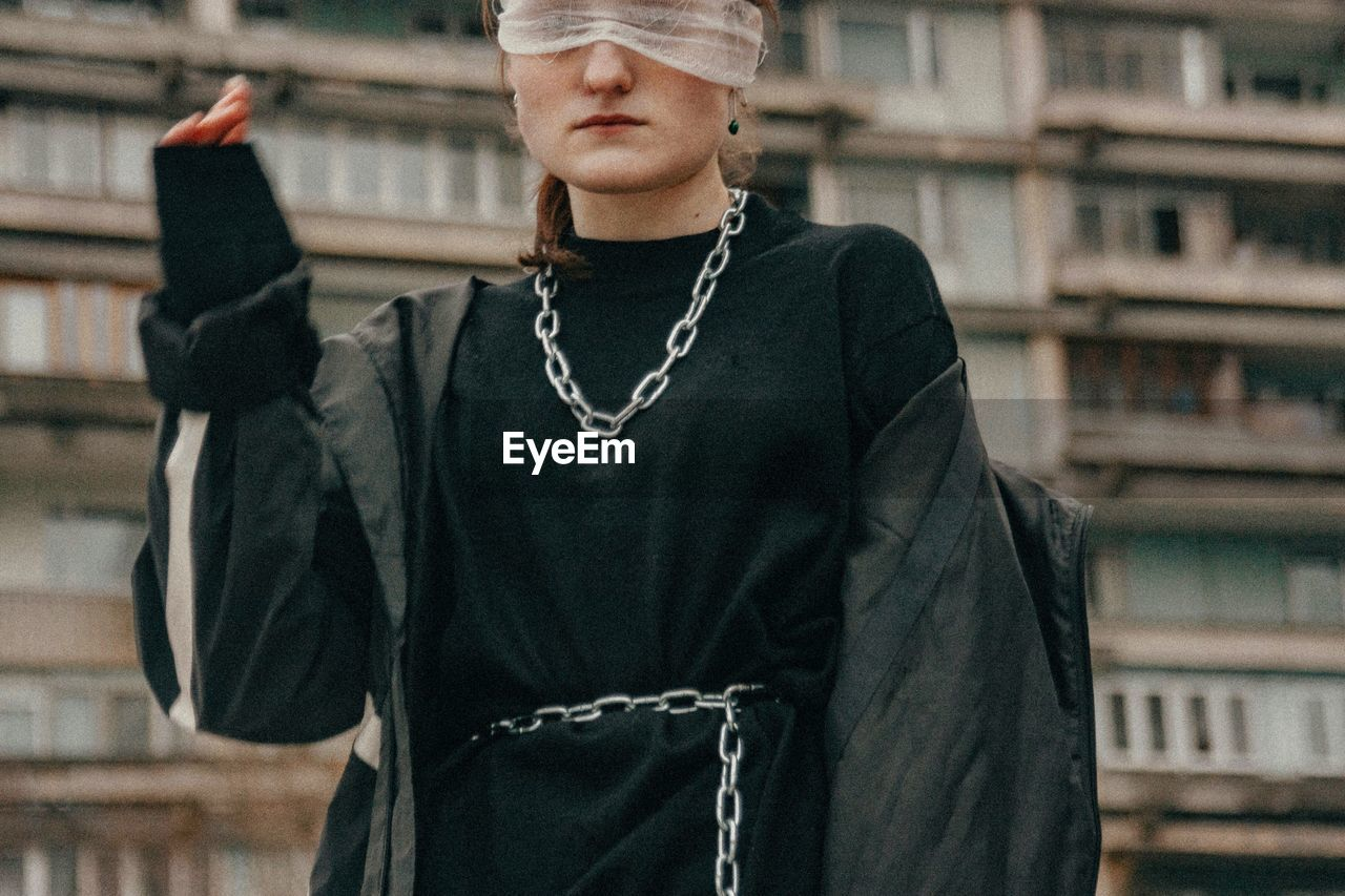 Midsection of woman with blindfold standing against building