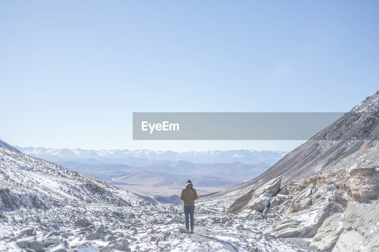 mountain, beauty in nature, scenics - nature, one person, leisure activity, sky, lifestyles, mountain range, non-urban scene, rear view, real people, standing, adventure, tranquility, tranquil scene, landscape, nature, environment, day, copy space, outdoors, snowcapped mountain
