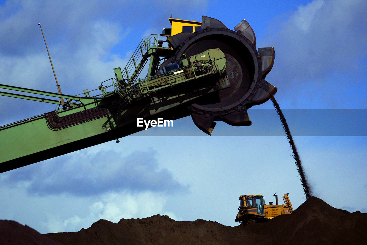 sky, machinery, cloud - sky, nature, low angle view, development, construction industry, industry, construction site, construction machinery, day, no people, earth mover, crane - construction machinery, outdoors, metal, equipment, architecture, transportation, blue, construction equipment, industrial equipment, quarry