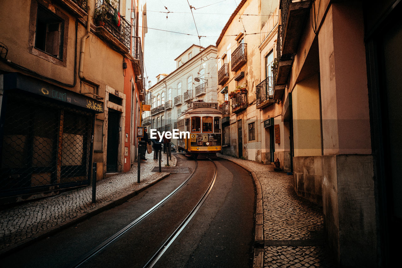 architecture, built structure, building exterior, transportation, city, railroad track, rail transportation, track, mode of transportation, building, street, cable car, direction, day, residential district, public transportation, incidental people, the way forward, nature, outdoors, alley