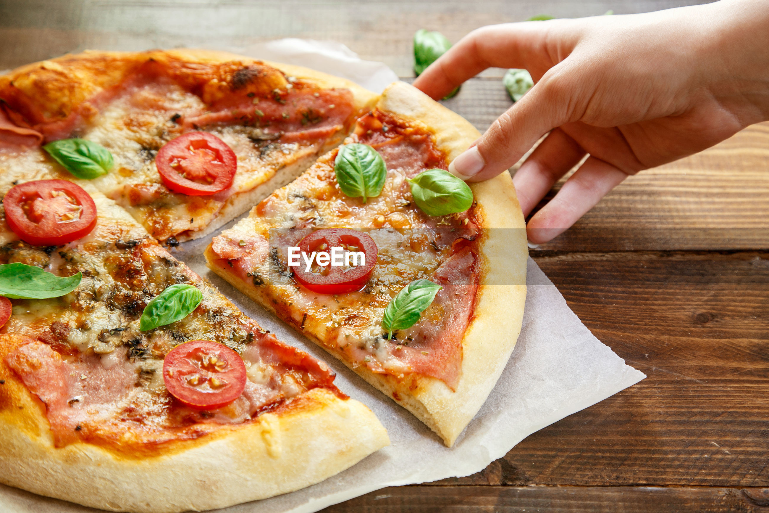 Cropped image of hand holding fresh margherita pizza with salami on wooden table