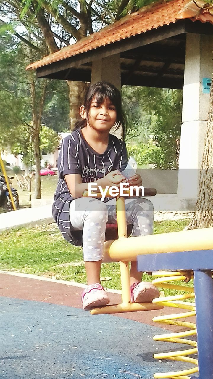 real people, front view, full length, leisure activity, happiness, casual clothing, smiling, day, tree, childhood, boys, mid adult women, outdoors, togetherness, sitting, elementary age, lifestyles, two people, looking at camera, young adult, park - man made space, architecture, young women, bonding, built structure, portrait