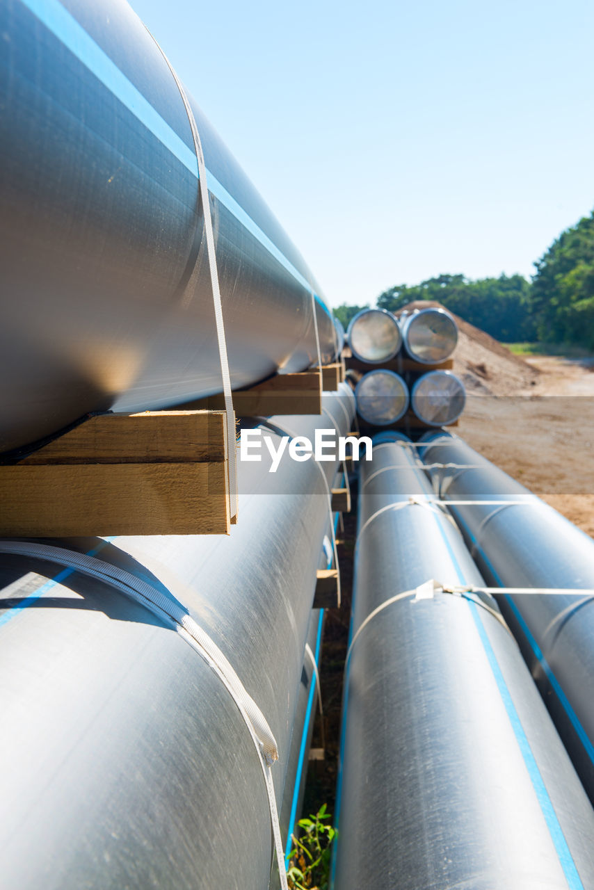 day, sky, pipe - tube, clear sky, nature, fuel and power generation, industry, sunlight, no people, outdoors, low angle view, architecture, metal, built structure, blue, pipe, environment, agriculture, roof, pipeline, silver colored