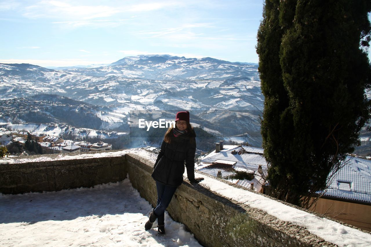 Portrait of smiling woman standing by retaining wall against snowcapped mountain