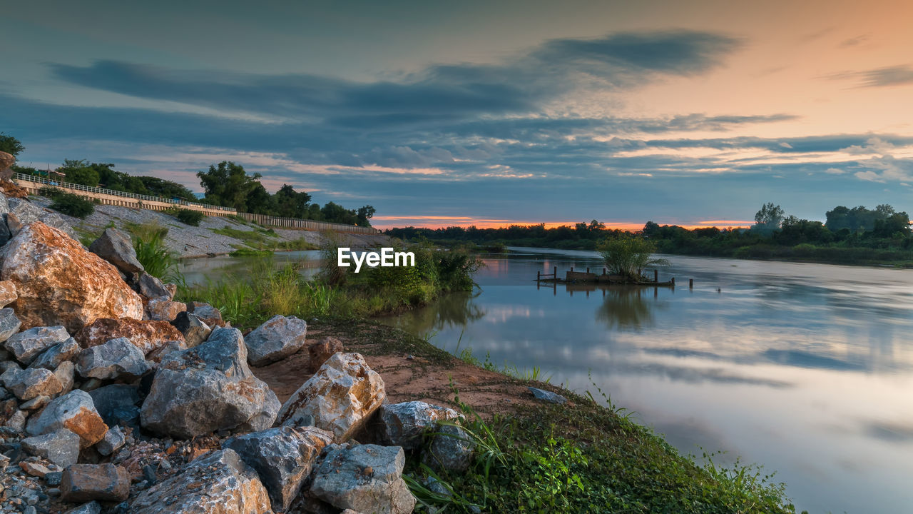 sky, water, cloud - sky, rock, solid, beauty in nature, rock - object, scenics - nature, nature, tranquility, sunset, lake, tranquil scene, plant, no people, tree, reflection, non-urban scene, outdoors