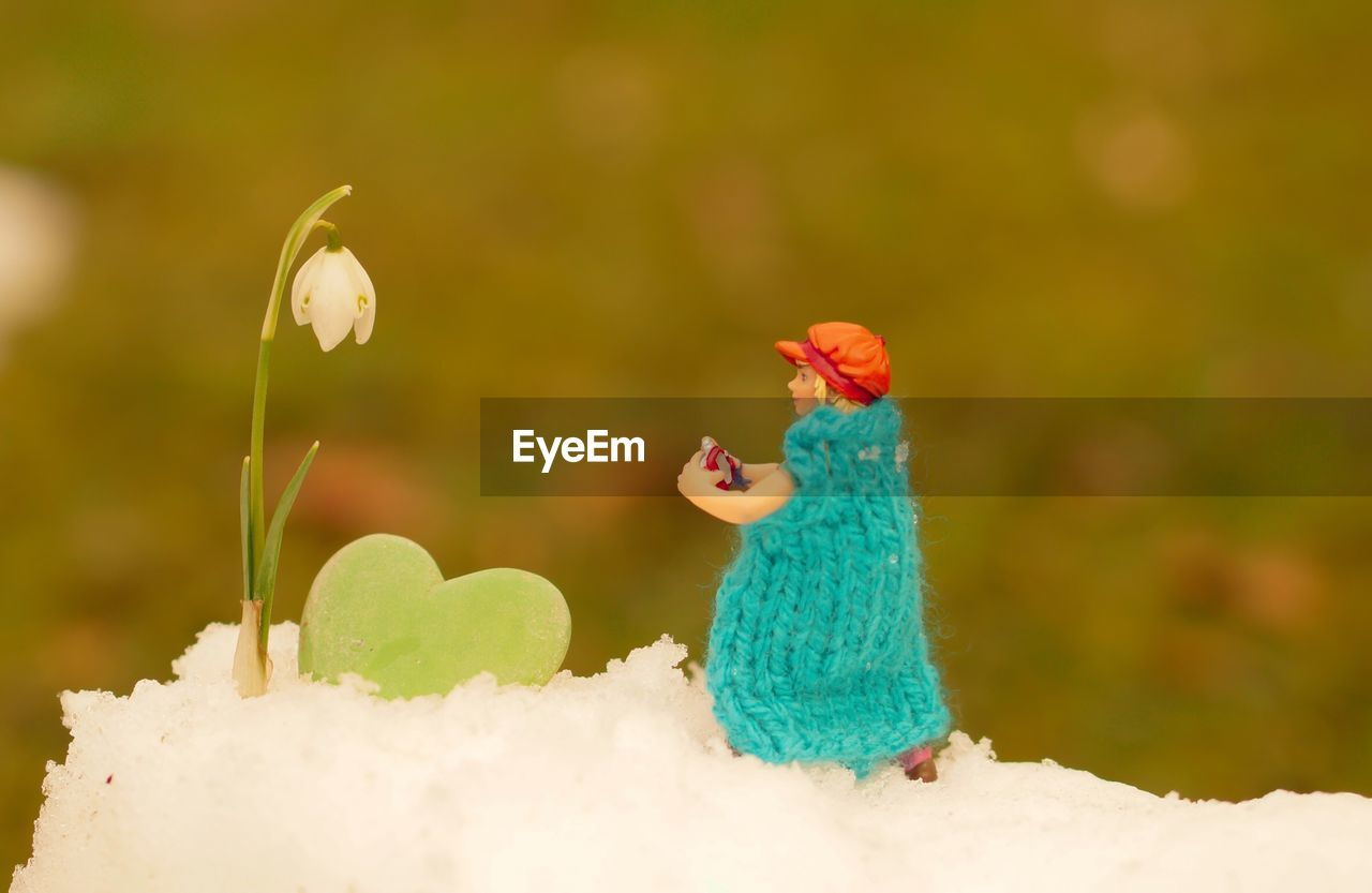 Close-up of figurine by snowdrop flower on snow