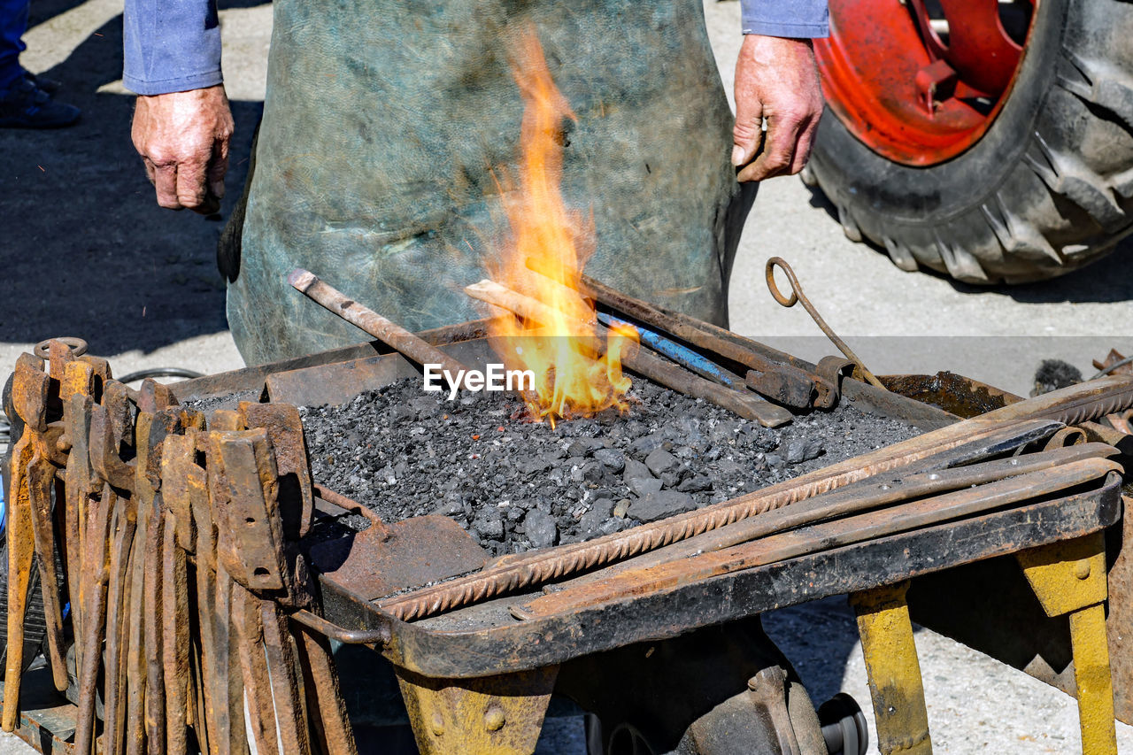 Midsection Of Man Heating Metal In Workshop
