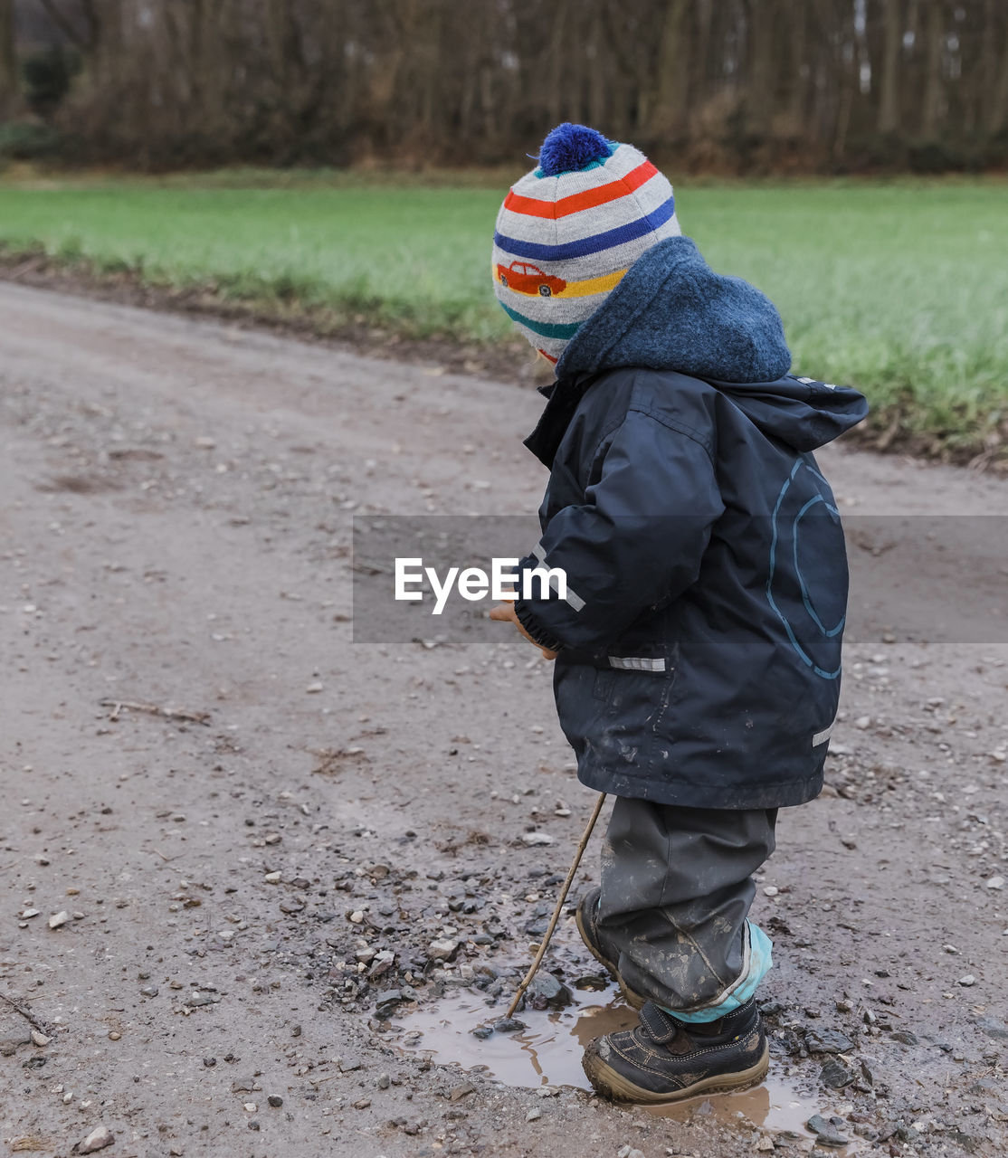 Side View Of Girl Standing By Puddle On Dirt Road