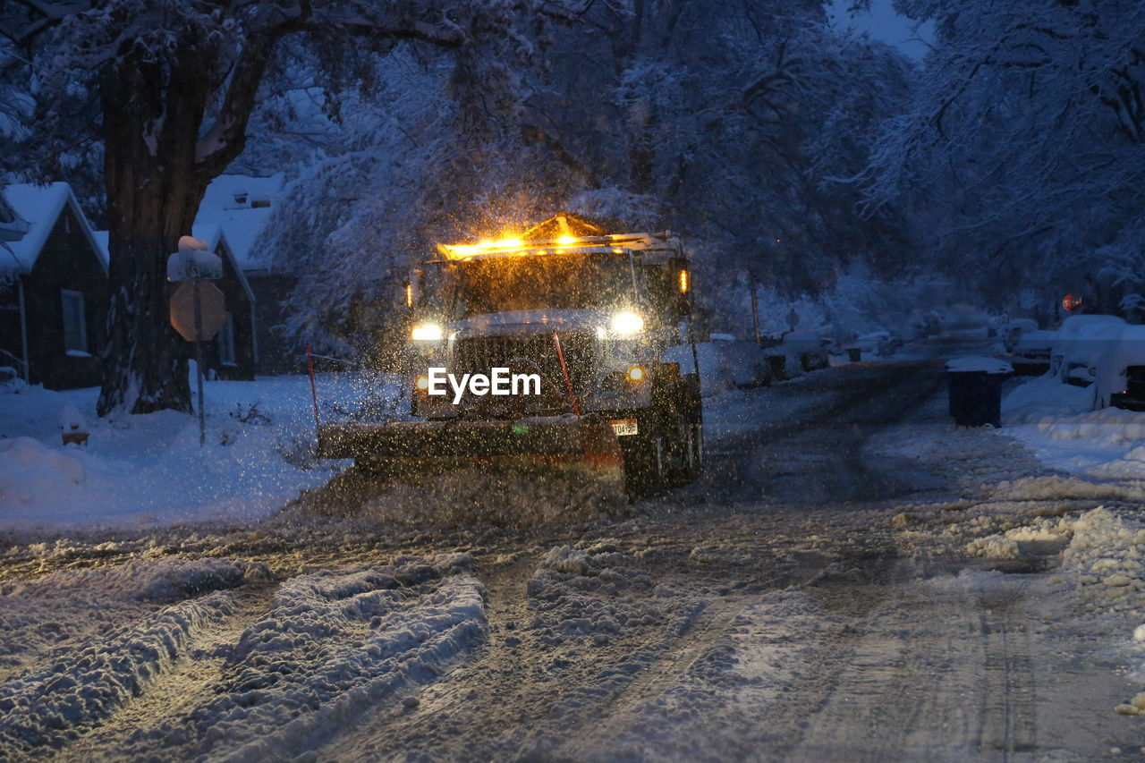 Snowplow On Road During Blizzard At Night