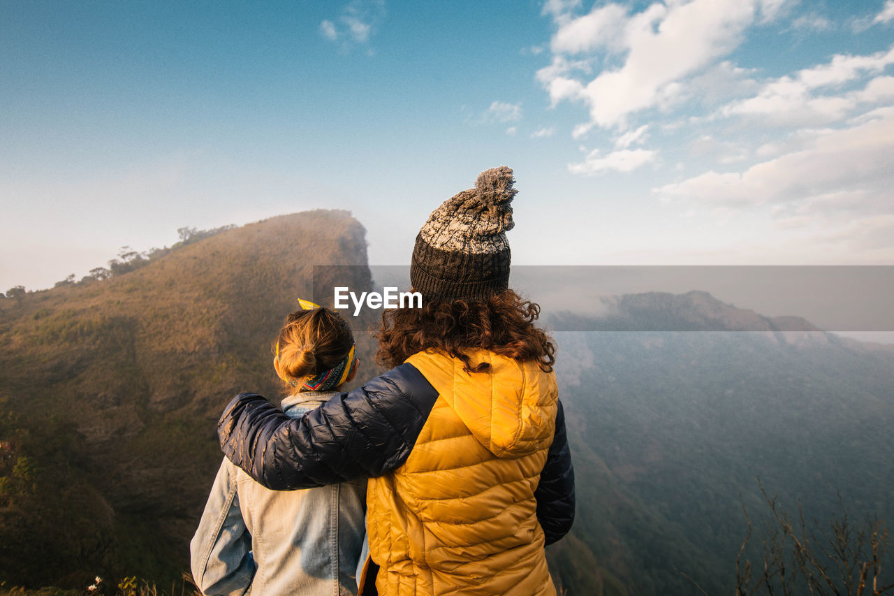 Rear View Of Mother And Daughter Standing On Mountain Against Sky