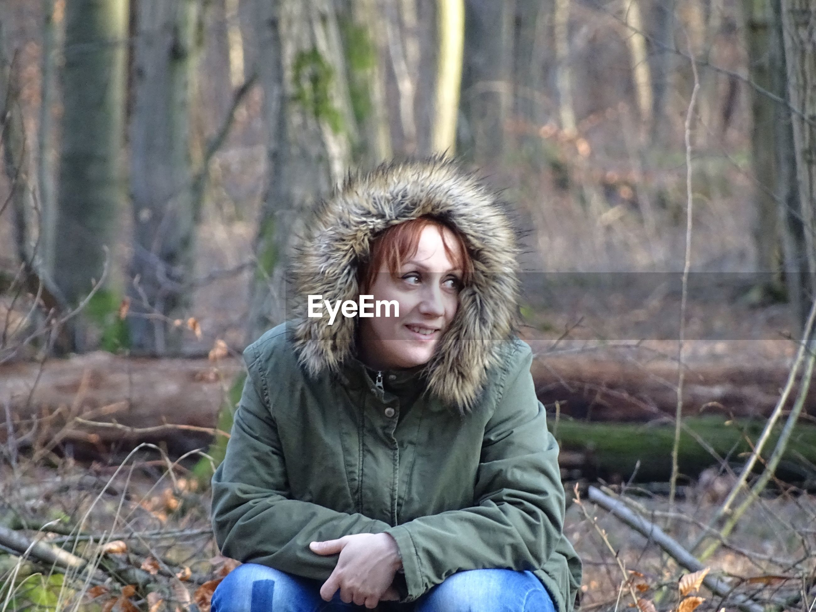 Smiling mid adult woman sitting in forest