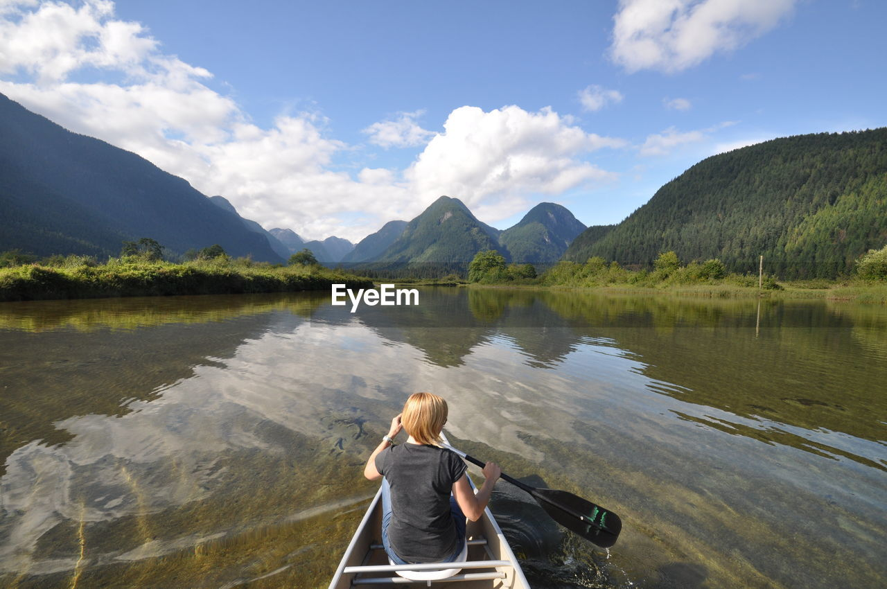 Rear View Of Woman On Canoe On Lake Against Mountain Range