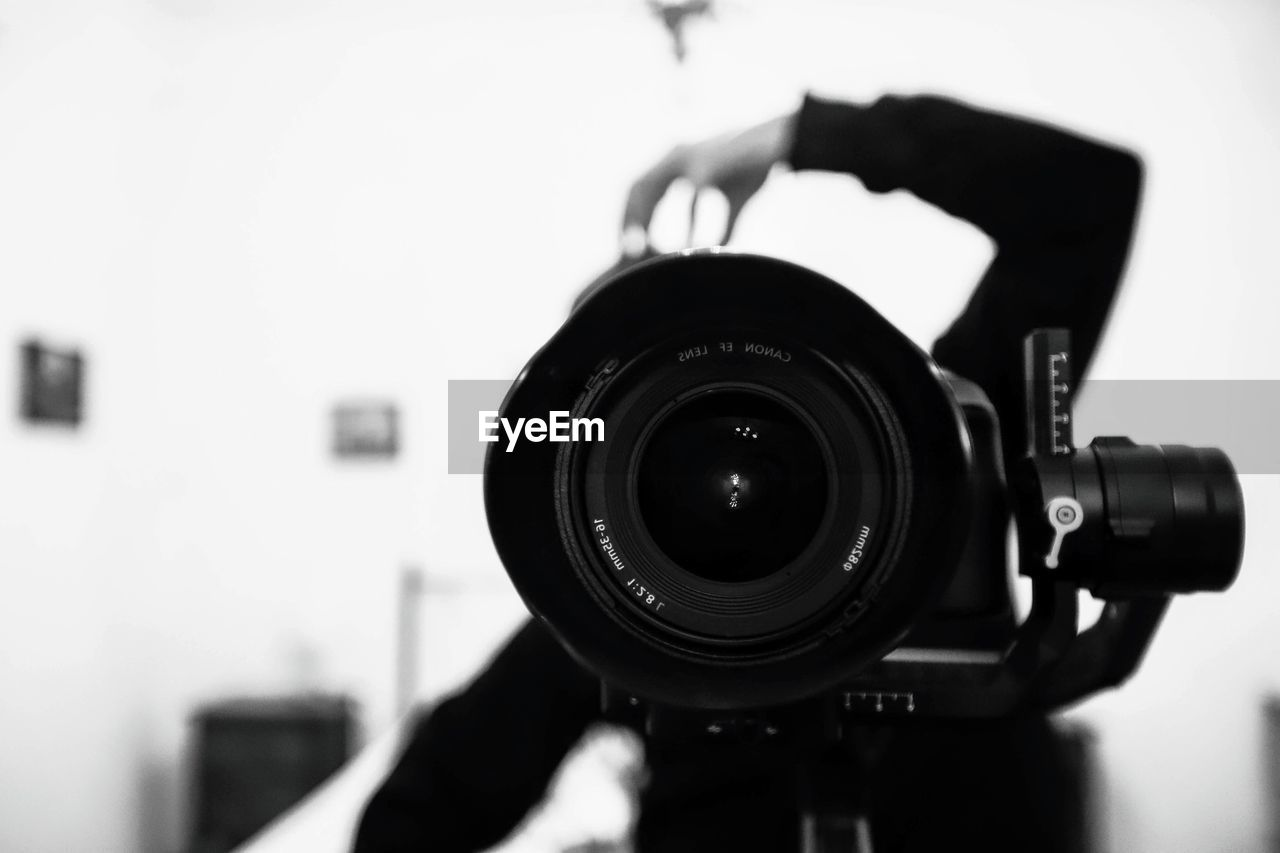 photography themes, technology, camera - photographic equipment, focus on foreground, digital camera, photographic equipment, camera, close-up, photographing, lens - optical instrument, indoors, activity, one person, black color, holding, day, equipment, security, communication, filming, photographer