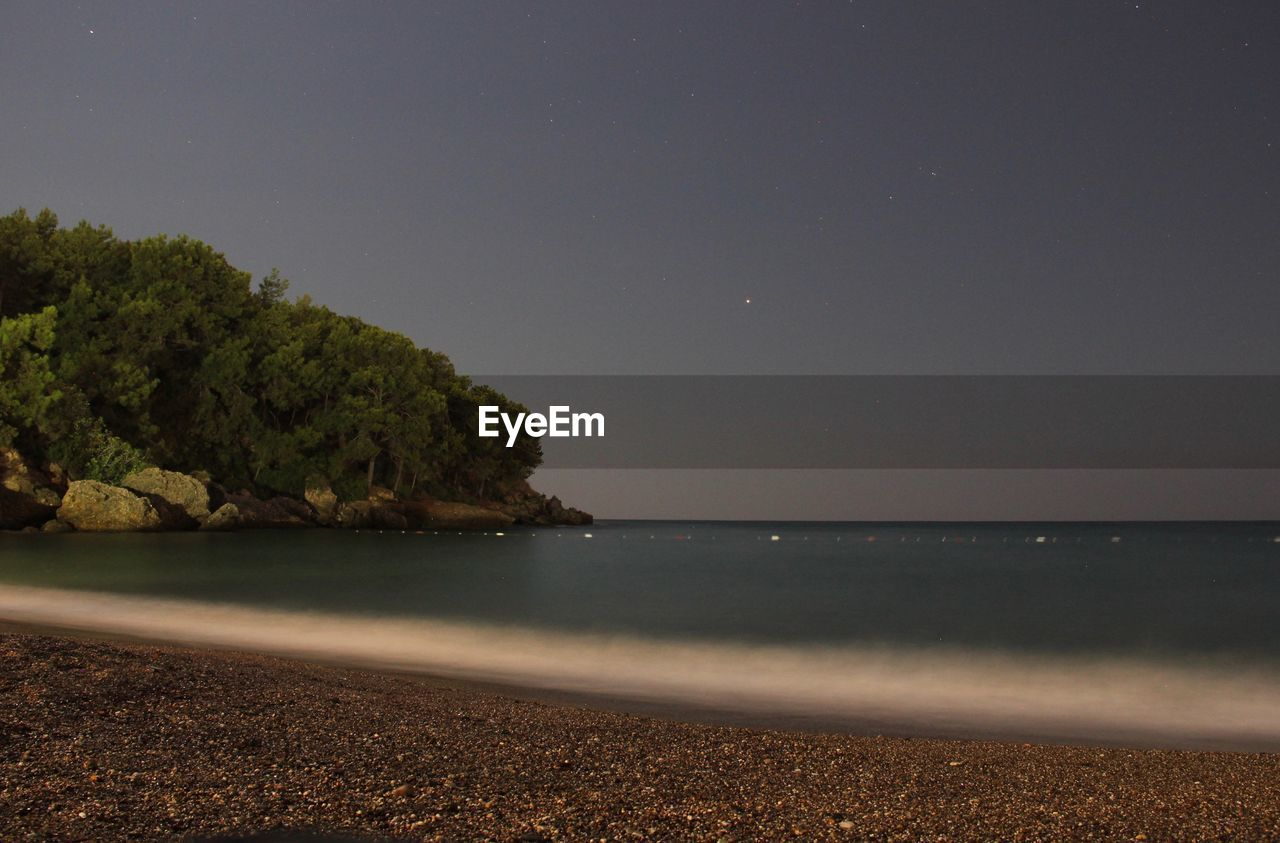 water, sea, sky, land, tree, tranquility, beauty in nature, beach, scenics - nature, nature, tranquil scene, no people, plant, horizon, clear sky, idyllic, night, horizon over water, copy space, outdoors