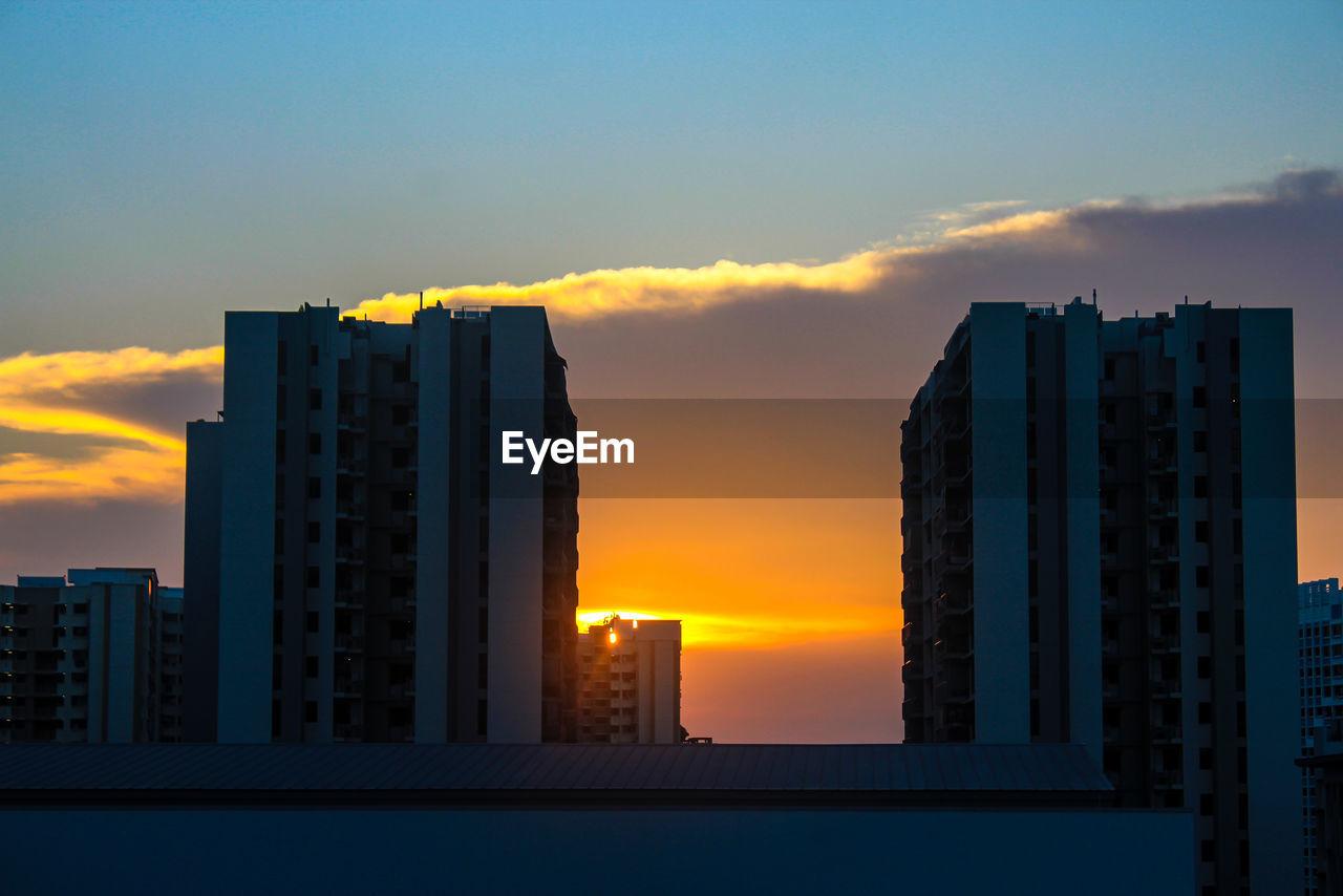 MODERN BUILDINGS AGAINST SKY AT SUNSET