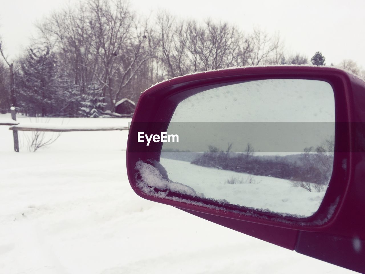 Reflection Of Snow Landscape In Car Rear View Mirror