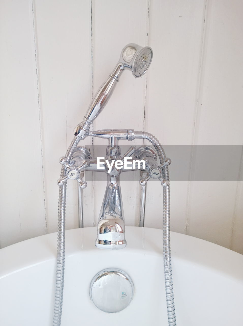 Shower head connected to faucet on bathtub
