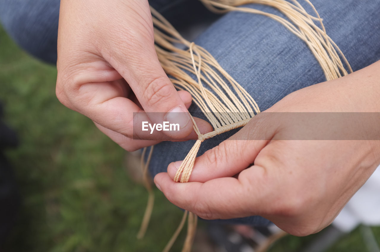 Close-up of hands tying strings