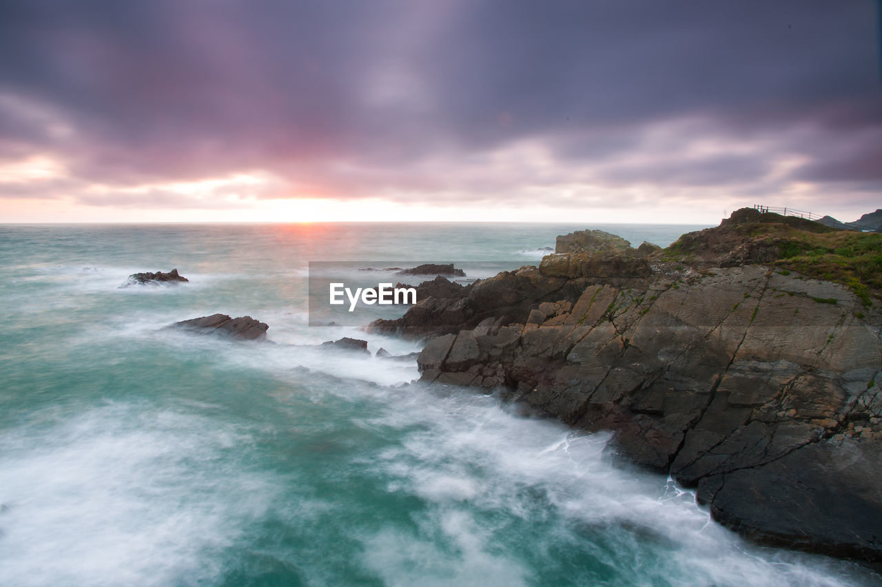 sky, sea, beauty in nature, water, scenics - nature, cloud - sky, rock, motion, solid, rock - object, horizon over water, long exposure, horizon, sunset, nature, idyllic, land, beach, tranquil scene, no people, outdoors, power in nature, flowing water, rocky coastline