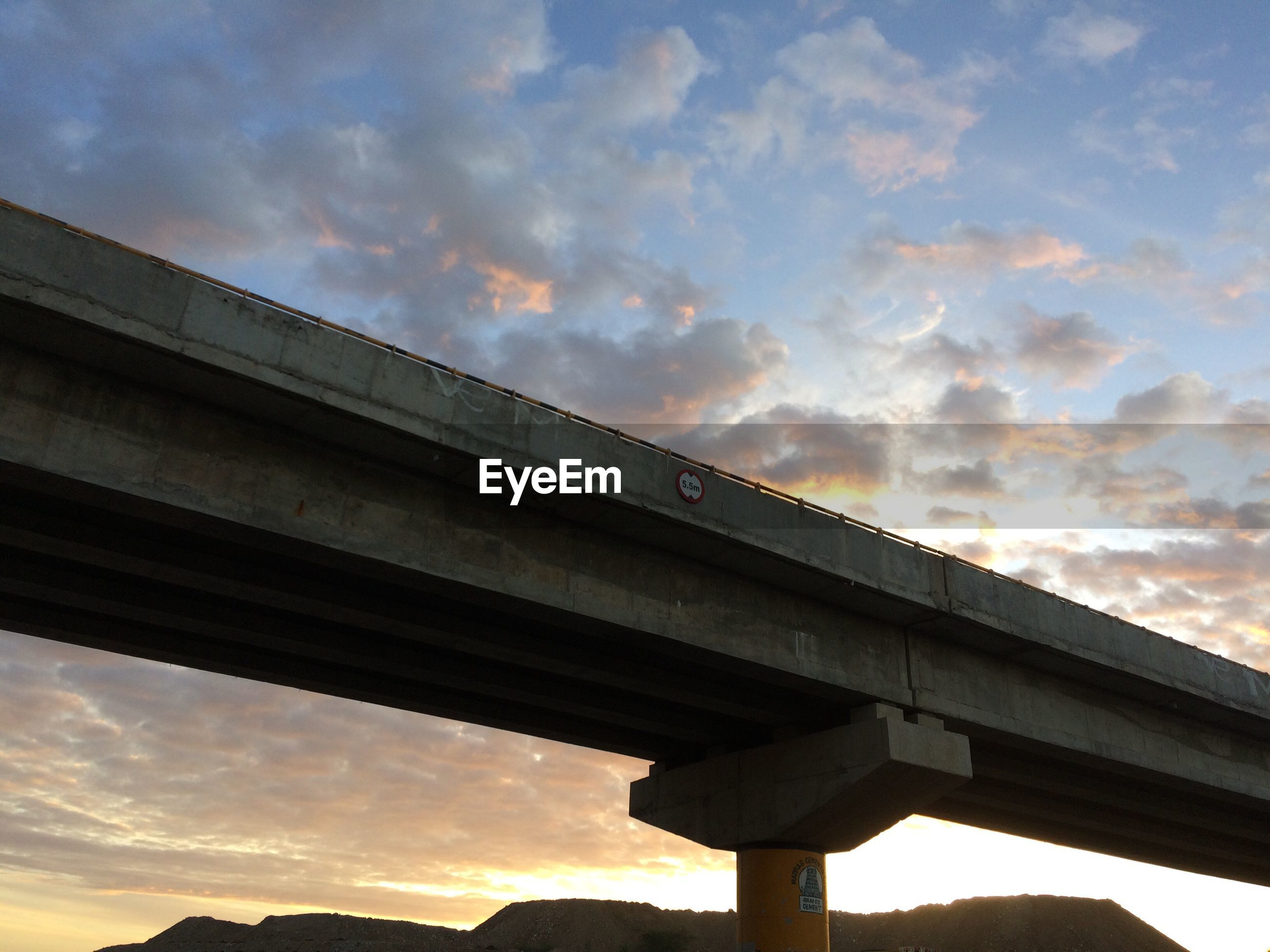 Low angle view of bridge against cloudy sky during sunset