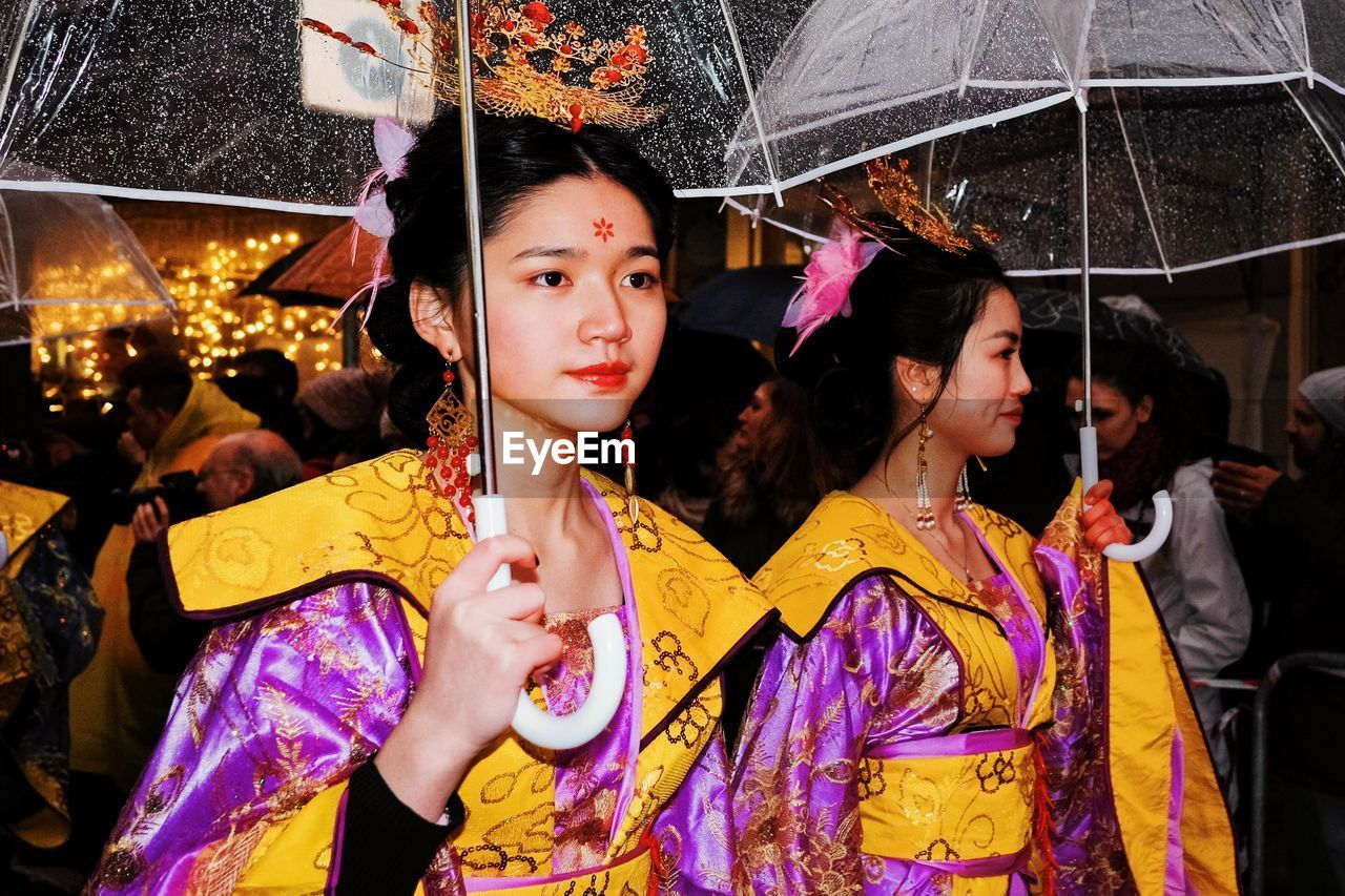 real people, women, group of people, lifestyles, incidental people, night, leisure activity, adult, umbrella, illuminated, people, celebration, traditional clothing, clothing, portrait, togetherness, females