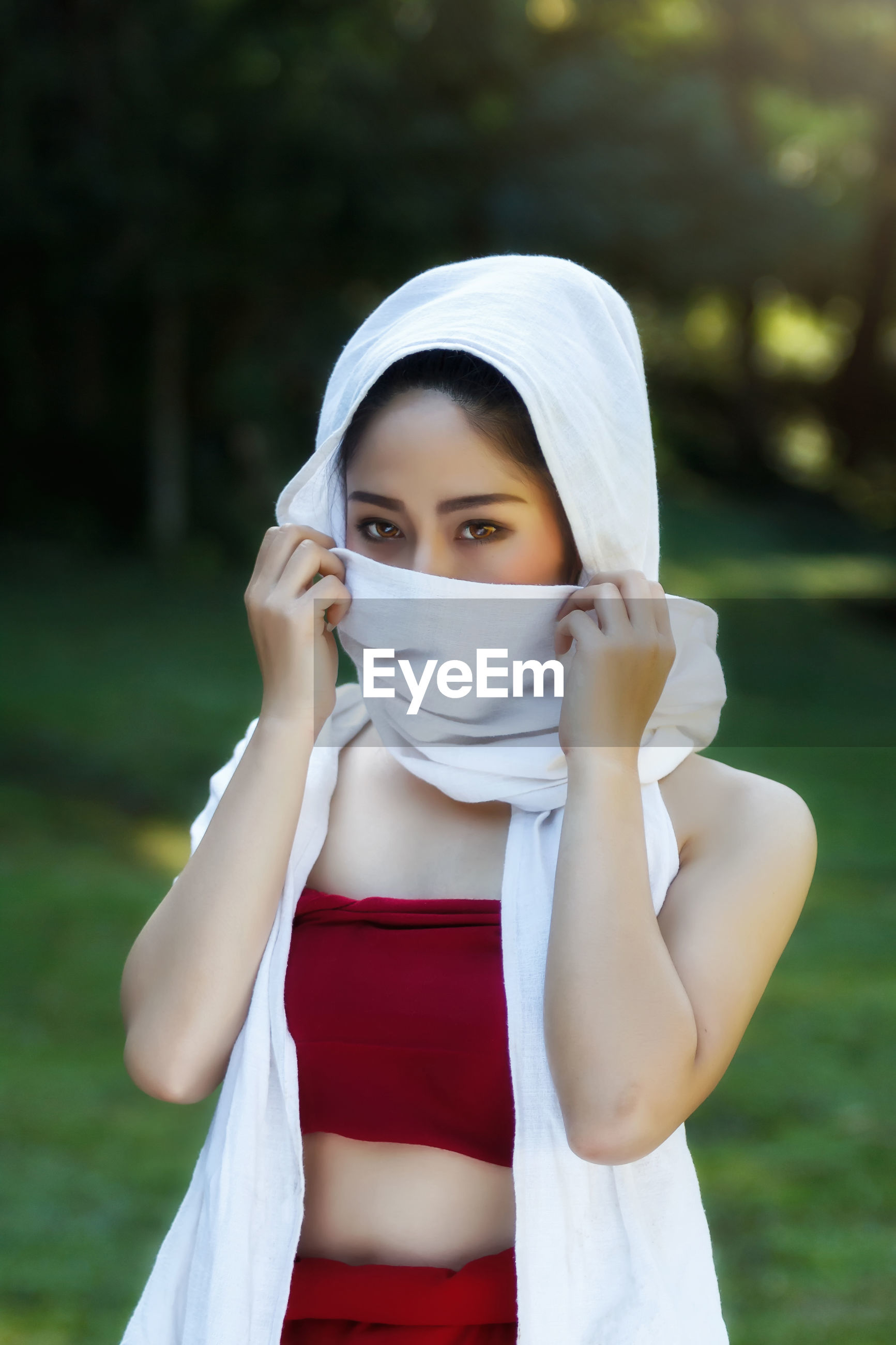 Portrait of young woman covering face with scarf while standing on field