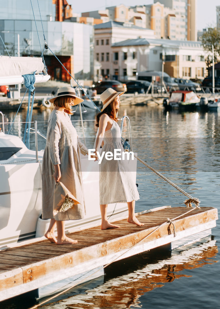 Two women friends walk along the pier along the boats and yachts in summer