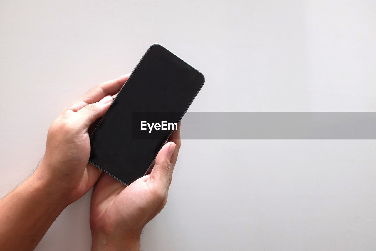 human hand, hand, human body part, one person, wireless technology, holding, copy space, technology, studio shot, indoors, connection, body part, real people, portable information device, communication, unrecognizable person, smart phone, lifestyles, white background, finger