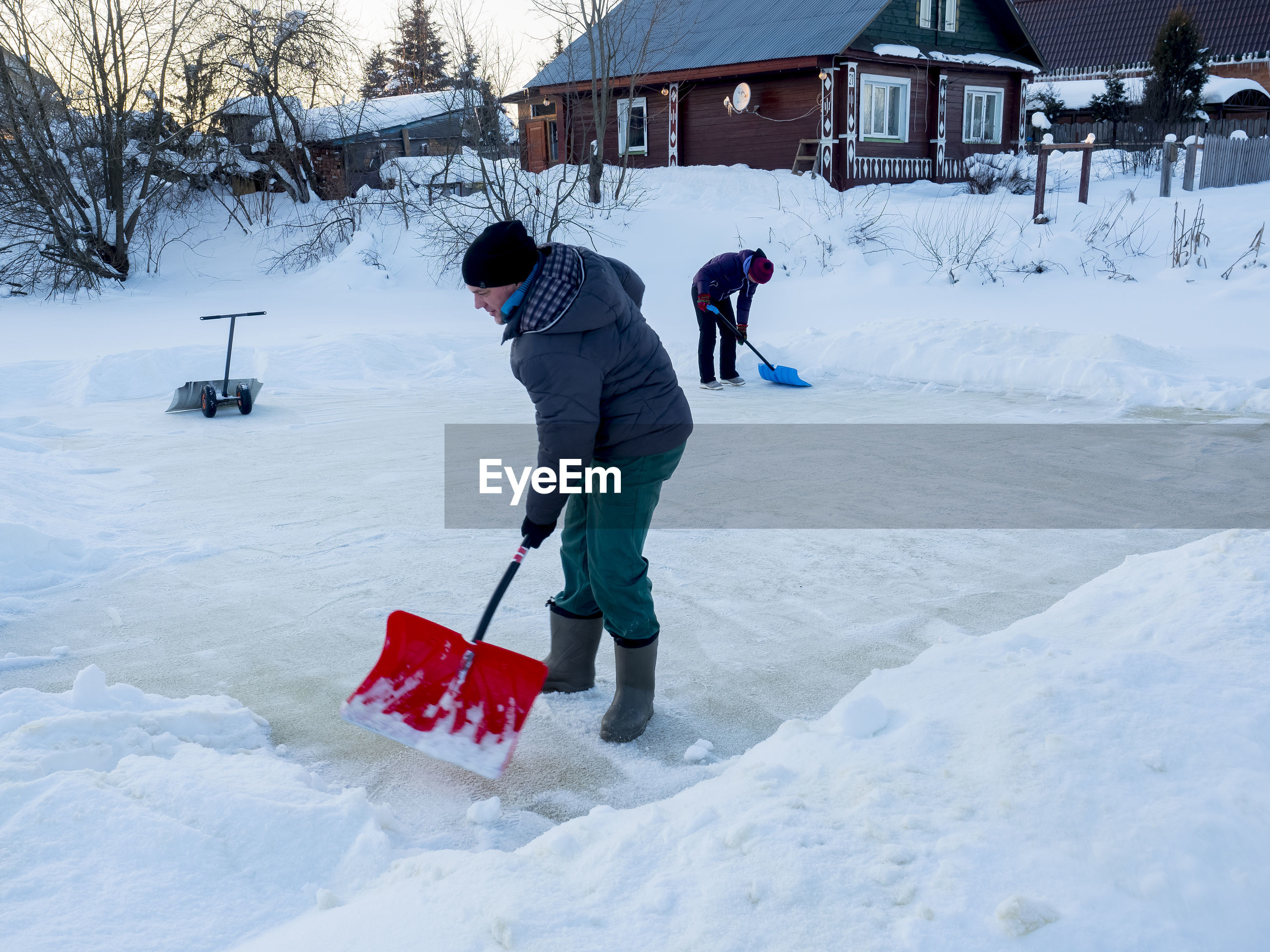 People cleaning snow with shovel on field
