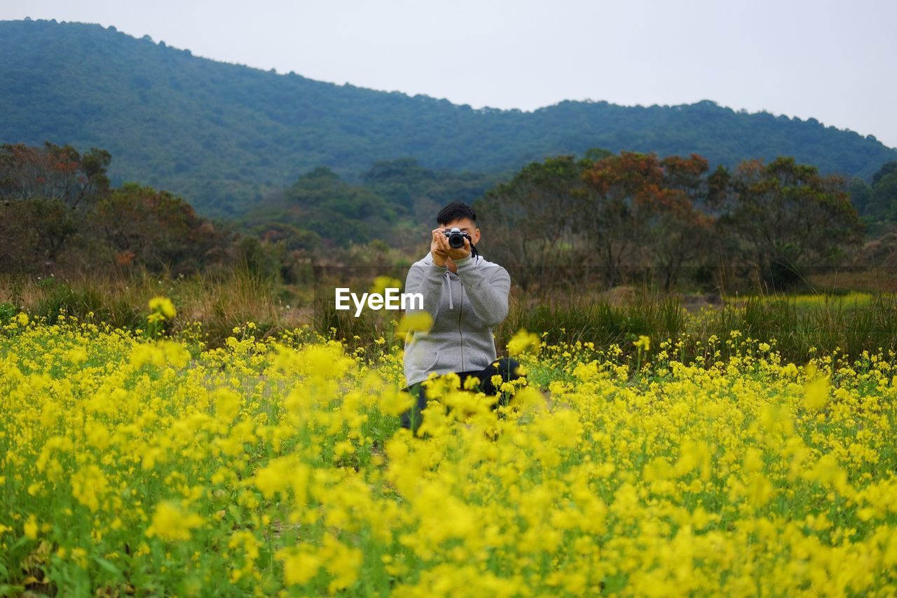 flower, field, nature, yellow, front view, one person, real people, beauty in nature, landscape, mid adult, oilseed rape, day, outdoors, plant, casual clothing, mountain, growth, standing, clear sky, looking at camera, sky, rural scene, young adult, portrait, tree, freshness, adult, adults only, people