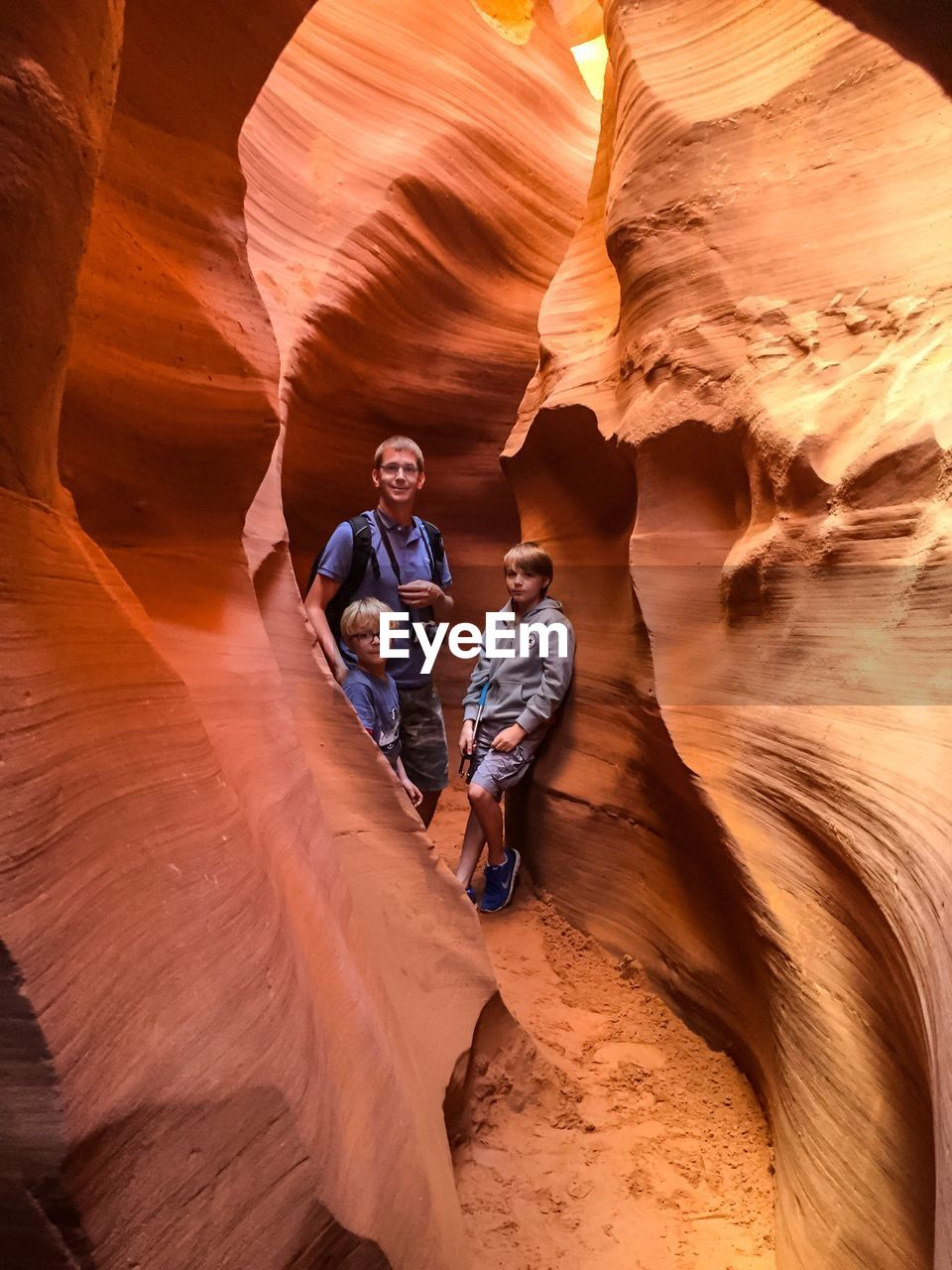 Portrait of father with sons standing amidst sandstones at antelope canyon