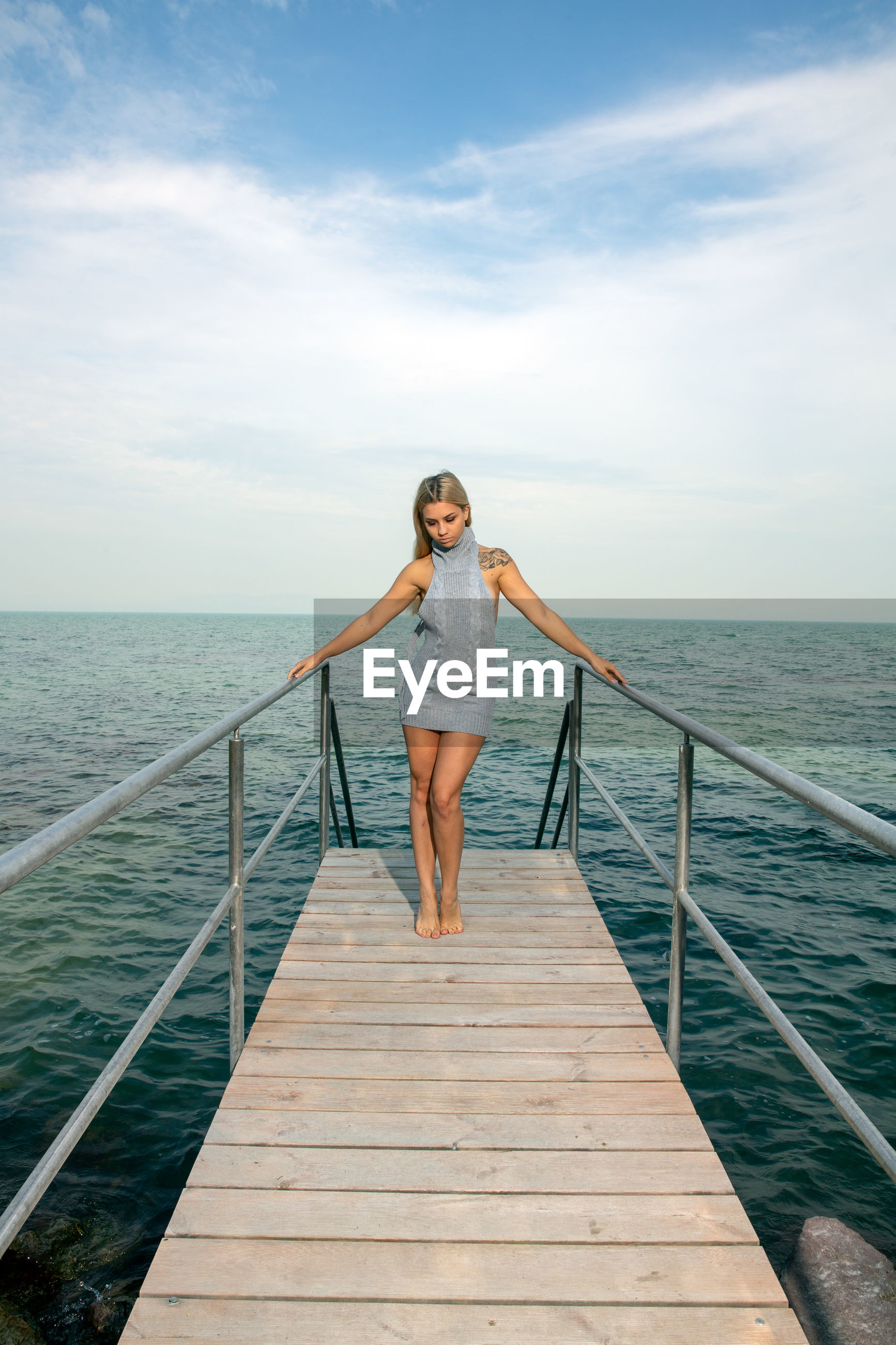 Full length of young woman standing on pier over sea