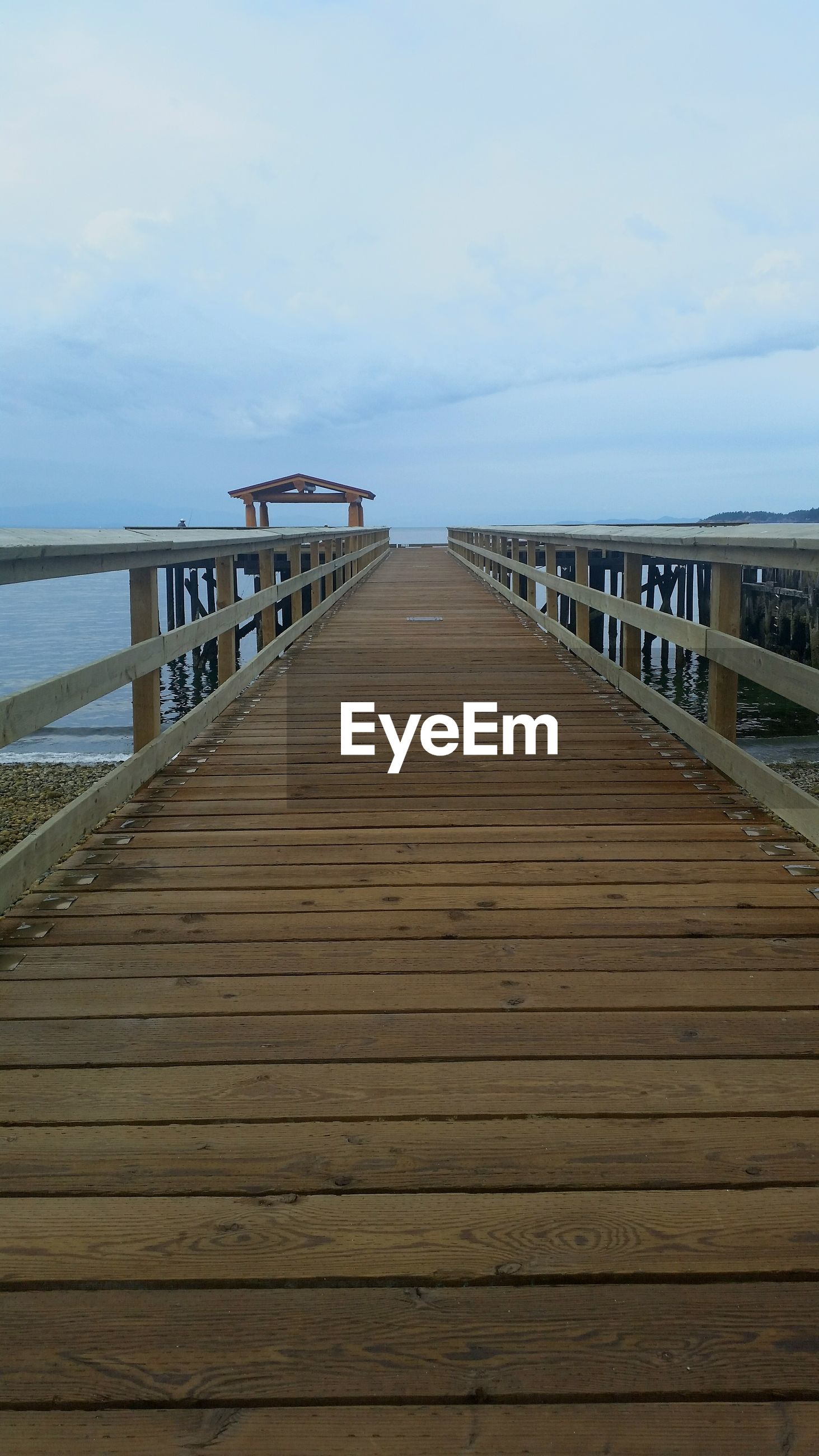 Wooden pier leading towards sea against cloudy sky