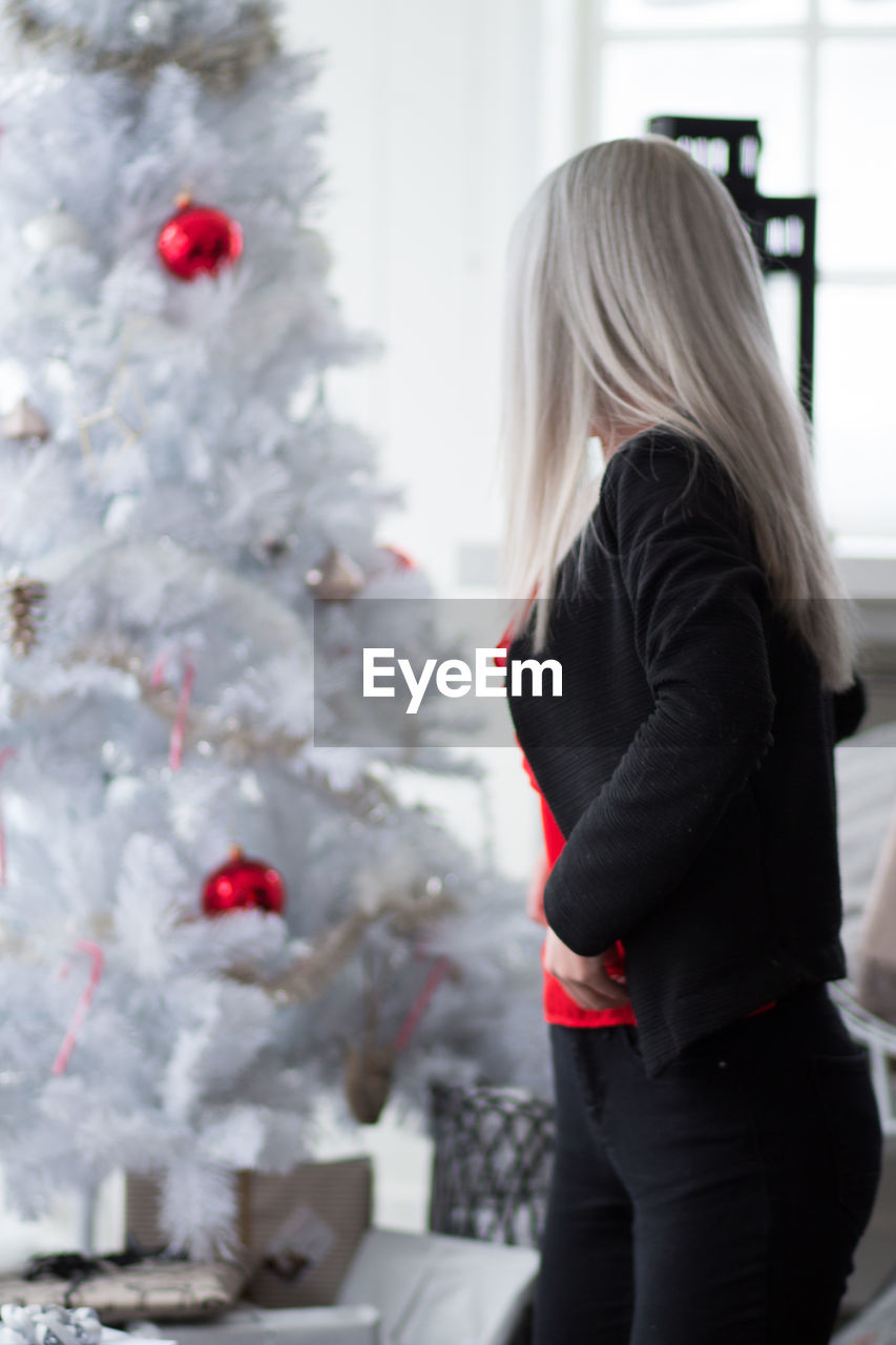 women, blond hair, hair, one person, real people, standing, lifestyles, focus on foreground, three quarter length, holiday, christmas, winter, rear view, long hair, females, christmas tree, hairstyle, girls, tree, warm clothing, christmas ornament
