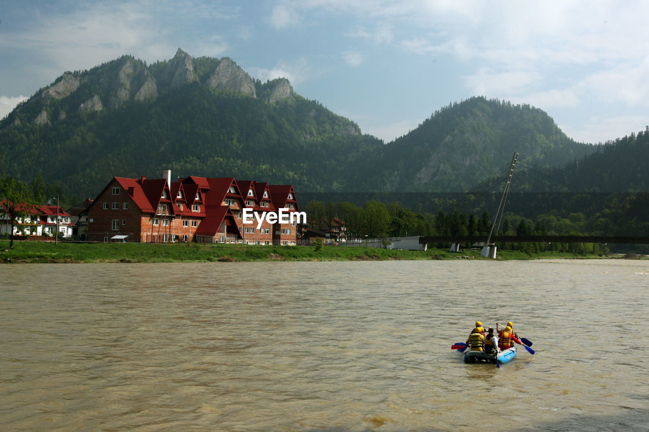 Scenic view of mountains in front of river against sky on sunny day