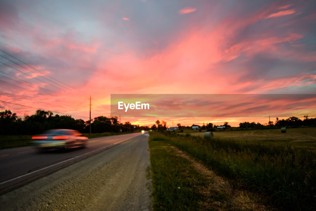 sunset, sky, cloud - sky, road, transportation, car, mode of transportation, orange color, motor vehicle, nature, motion, scenics - nature, beauty in nature, no people, landscape, street, plant, city, field, land, outdoors