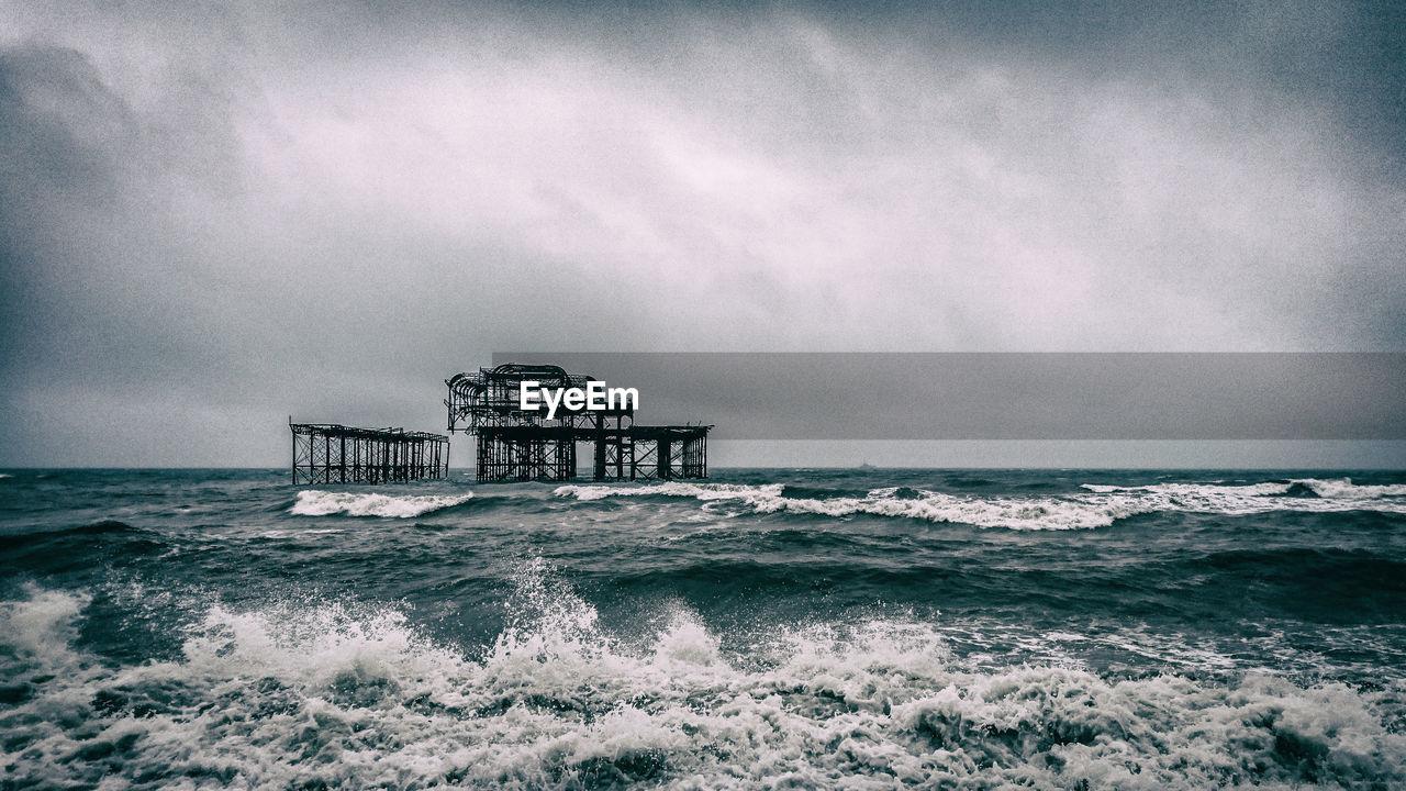 Old pier in sea against sky