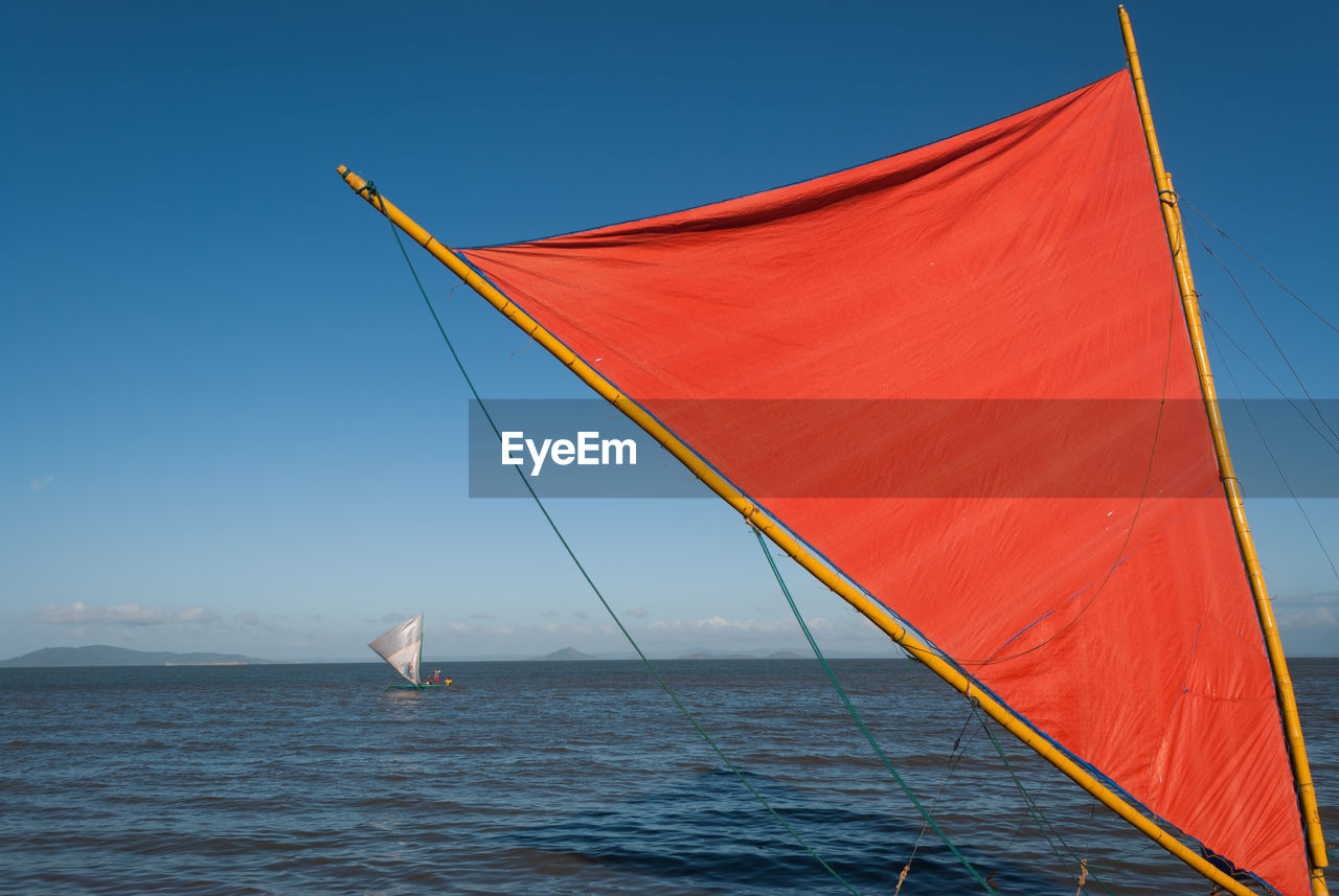 water, sky, sea, blue, day, nature, clear sky, no people, waterfront, outdoors, nautical vessel, flag, sailboat, canvas, beauty in nature, wind, environment, scenics - nature, red