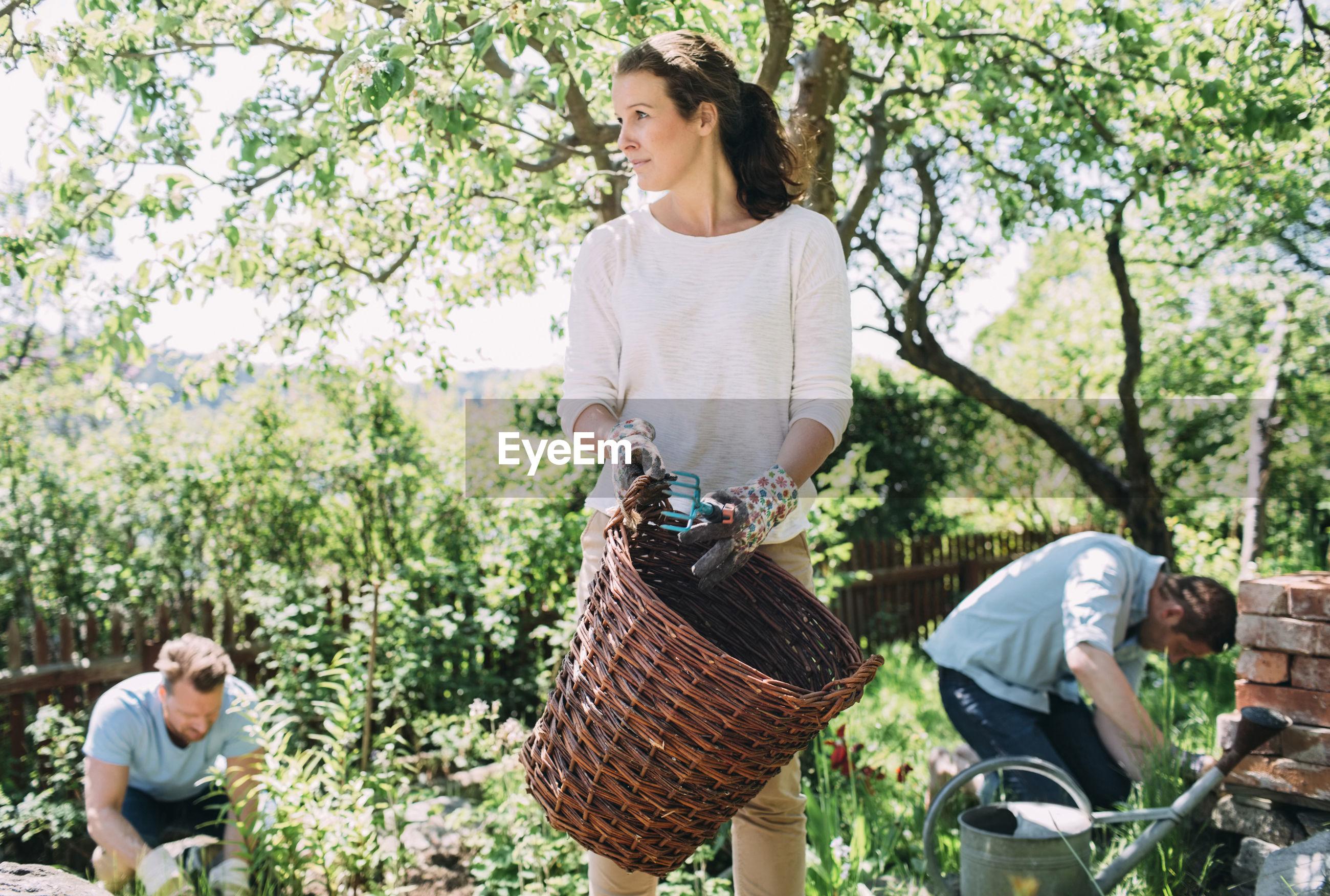 WOMAN STANDING IN BASKET AGAINST TREE