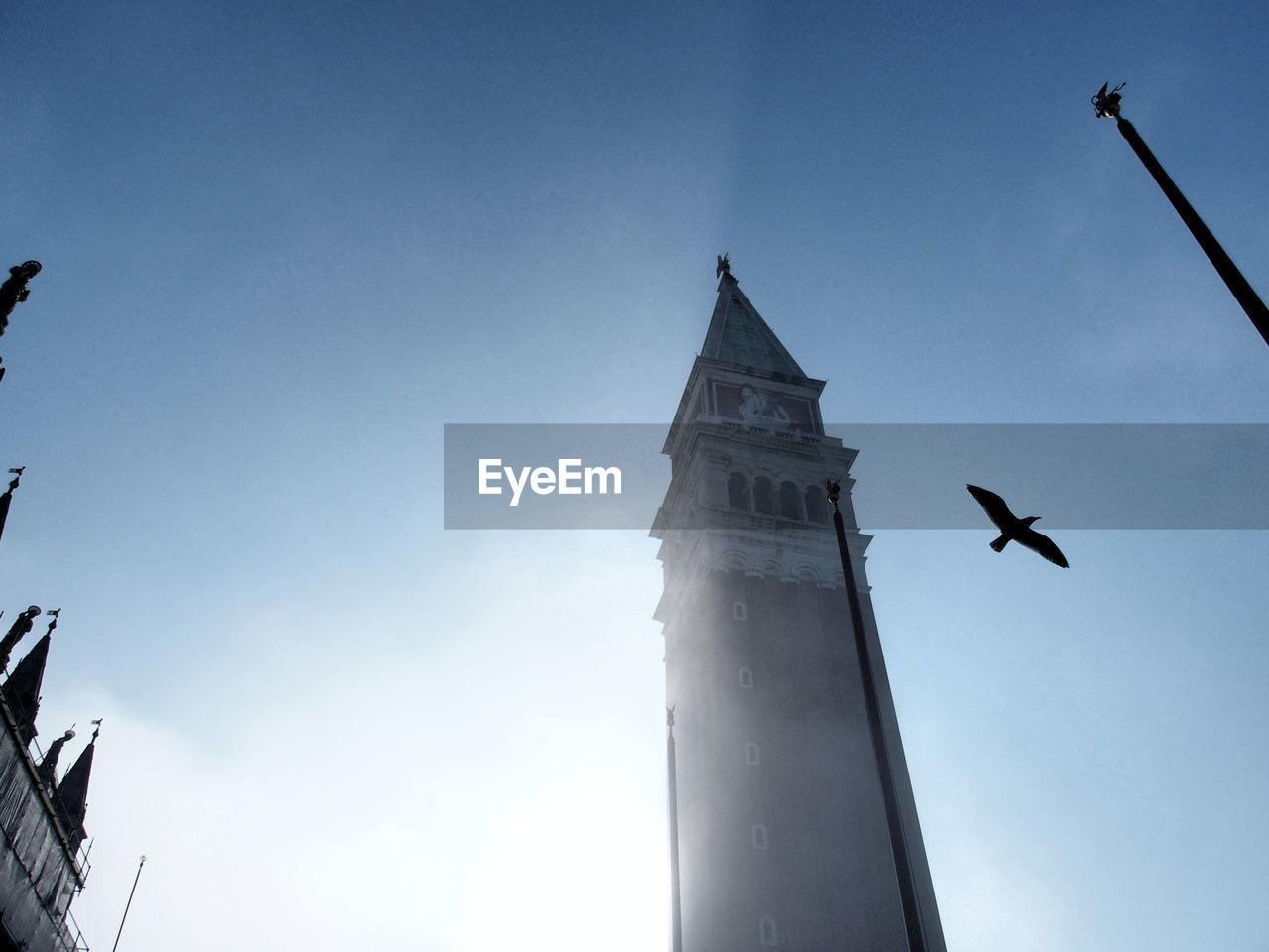 Bird flying by san marco campanile against sky