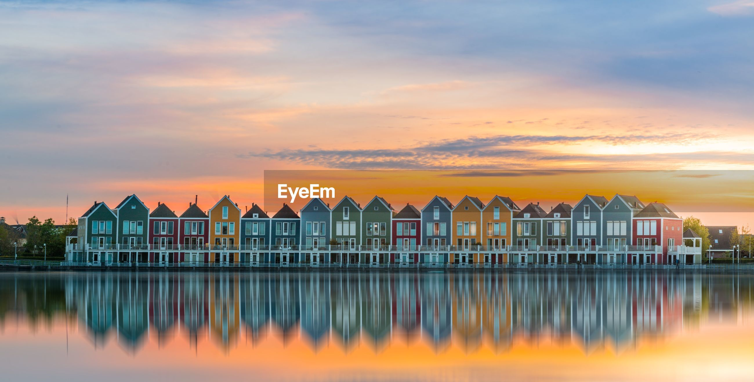 Multi colored houses by lake during sunset