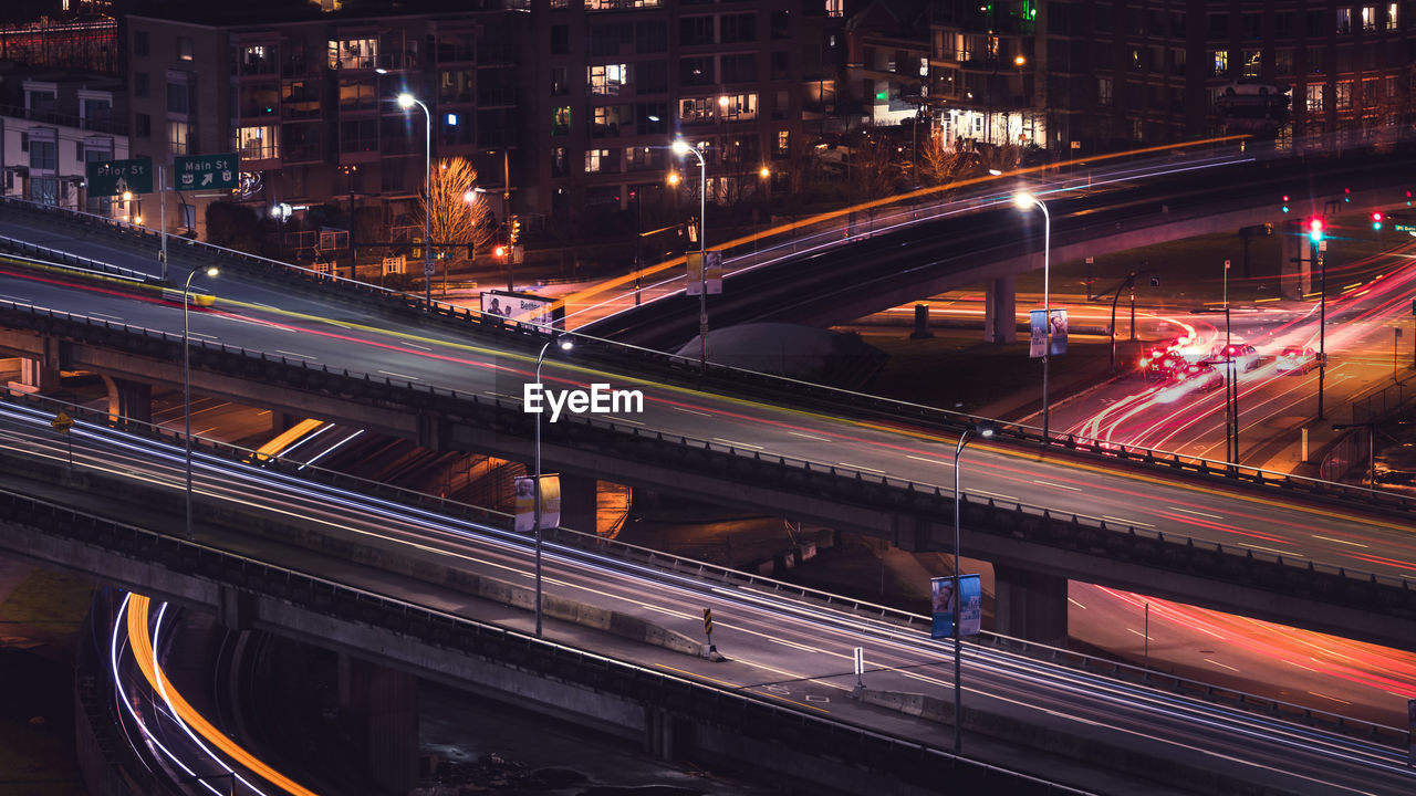 High angle view of light trails on bridge in city at night