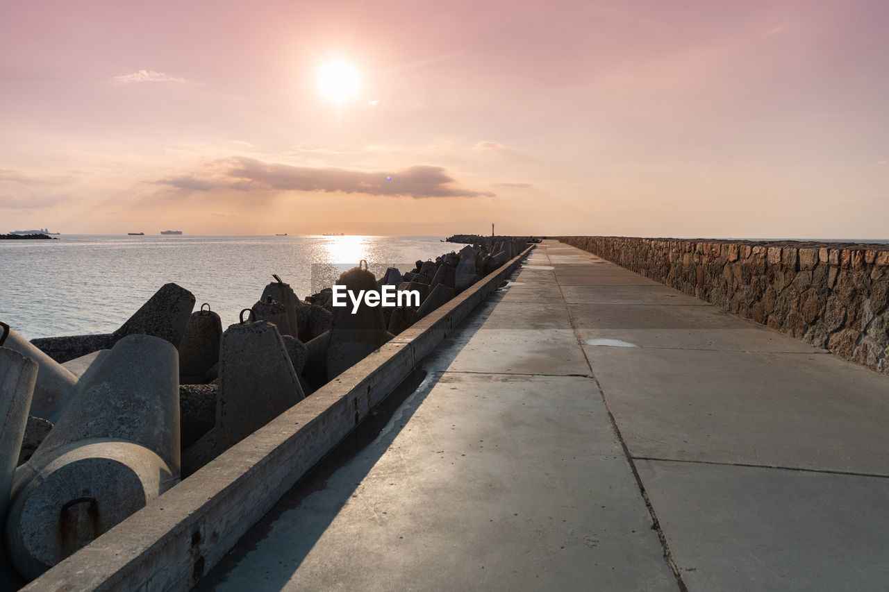 sky, water, sea, scenics - nature, beauty in nature, sunset, tranquility, tranquil scene, cloud - sky, nature, horizon, horizon over water, the way forward, direction, sun, sunlight, land, no people, railing, diminishing perspective, outdoors, groyne, concrete