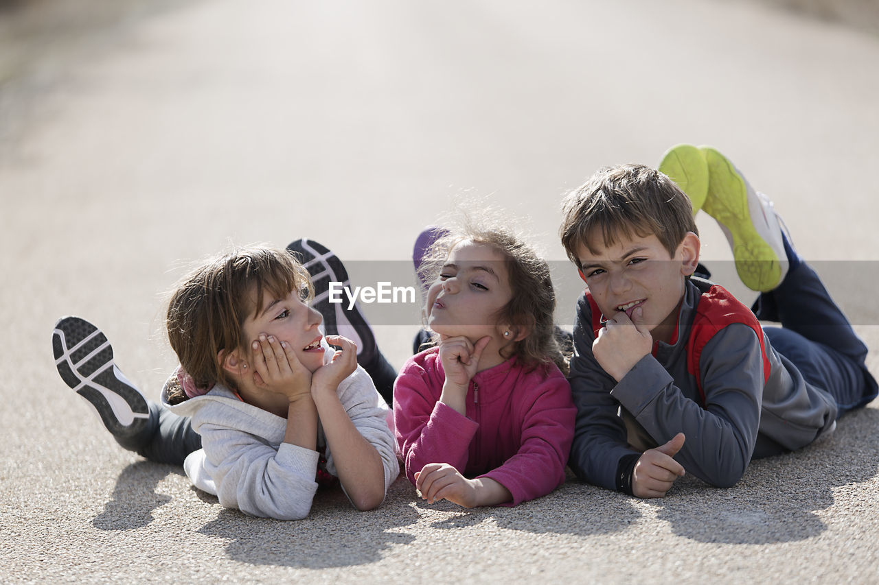Portrait Of Boy With Sisters Siblings Lying Down On Road
