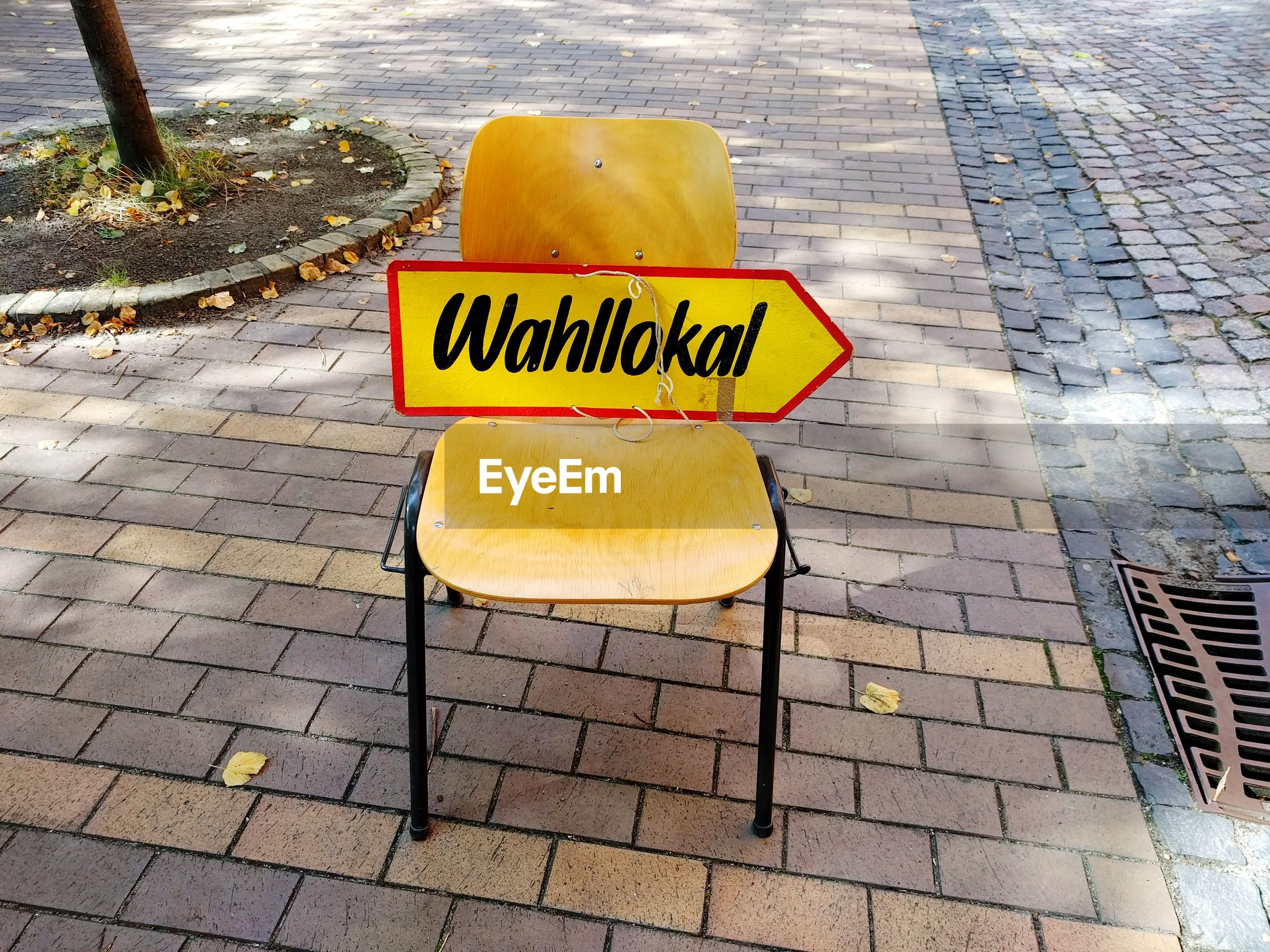 High angle view of chair with text on sidewalk