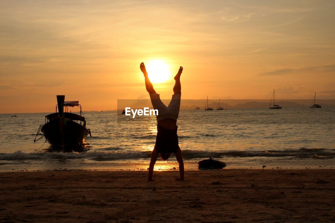 Full length of man practicing handstand at beach against sky during sunset
