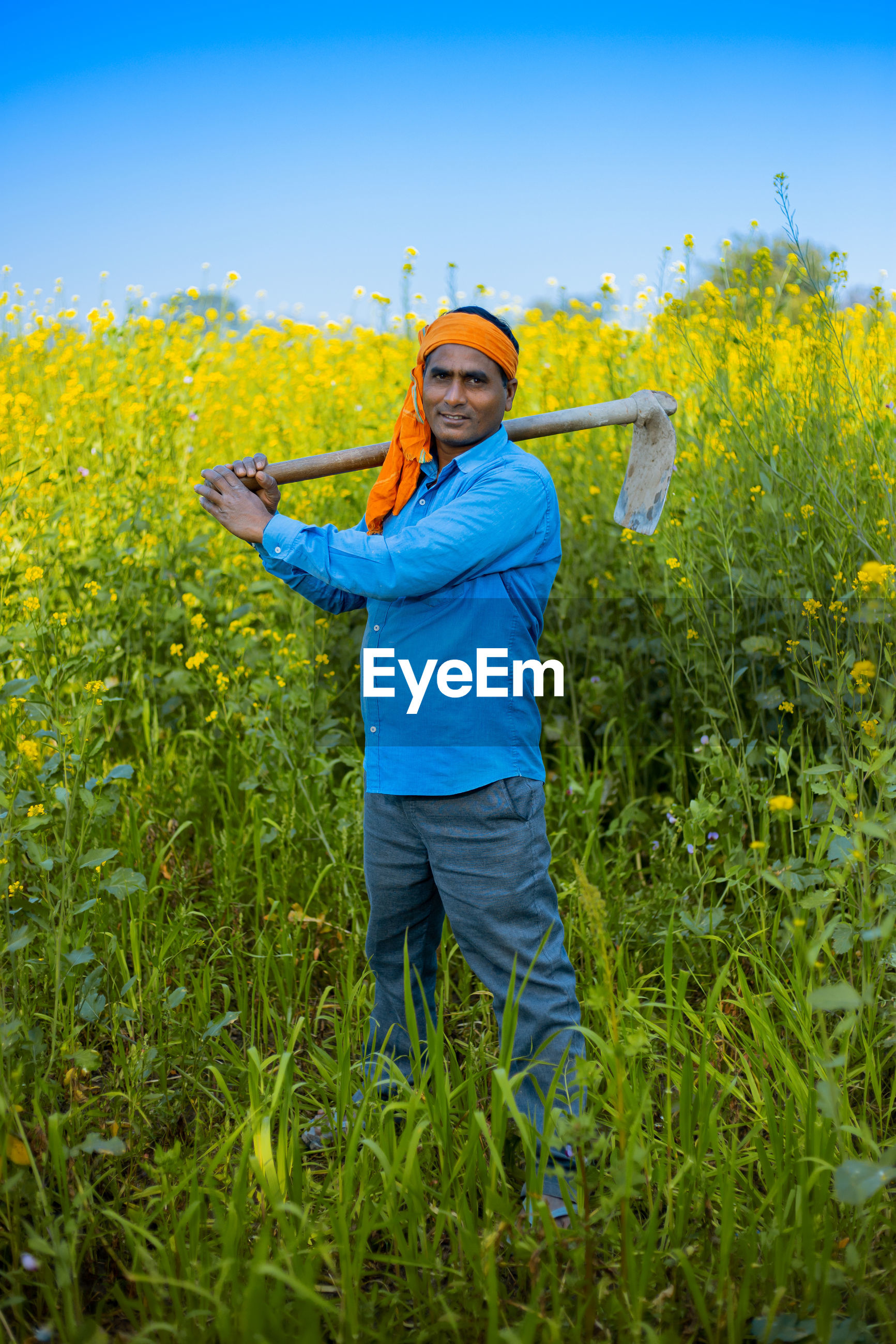 Portrait of farmer holding equipment while standing in farm