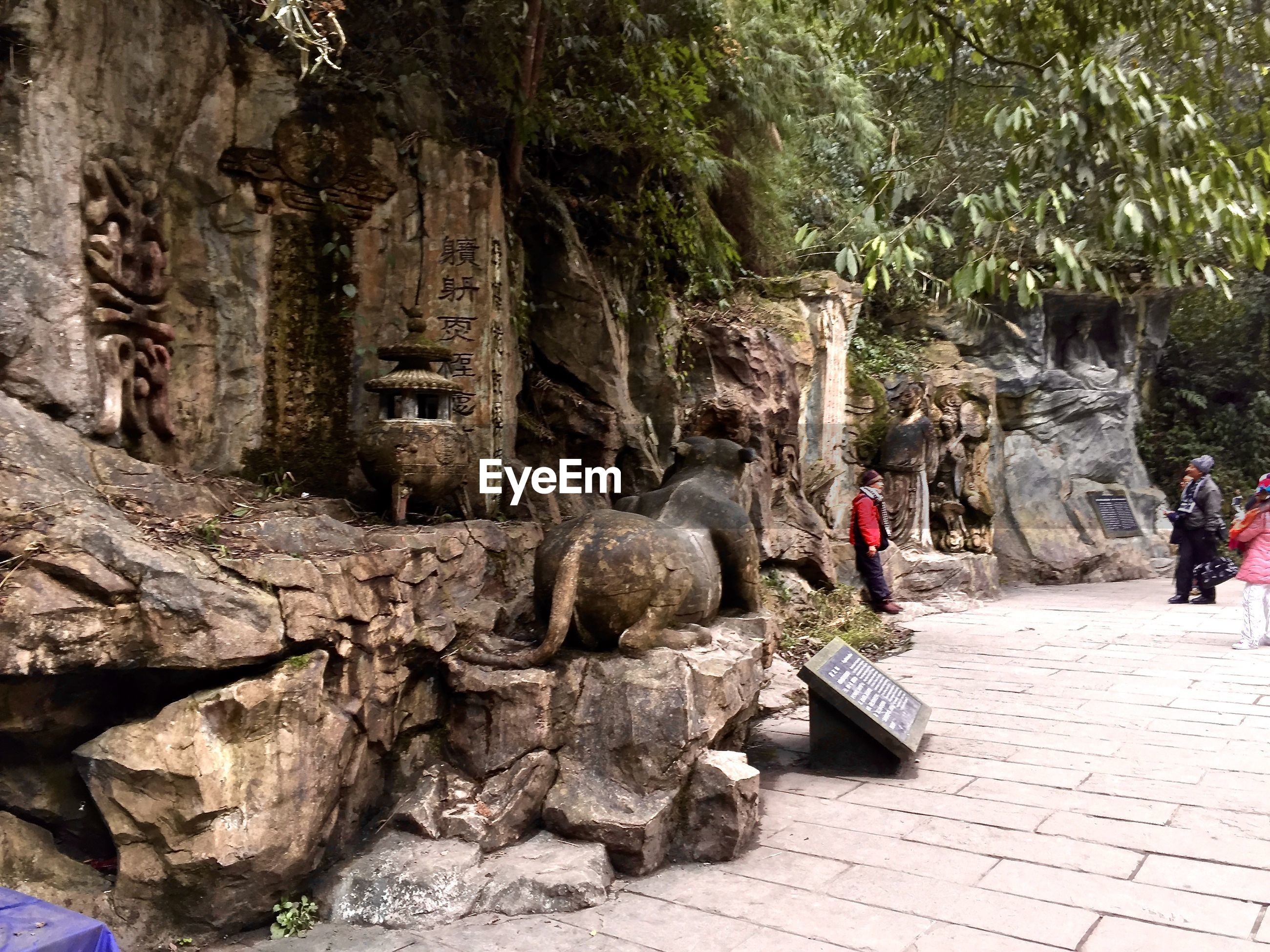 Tourists visiting carvings on rocks at historic site