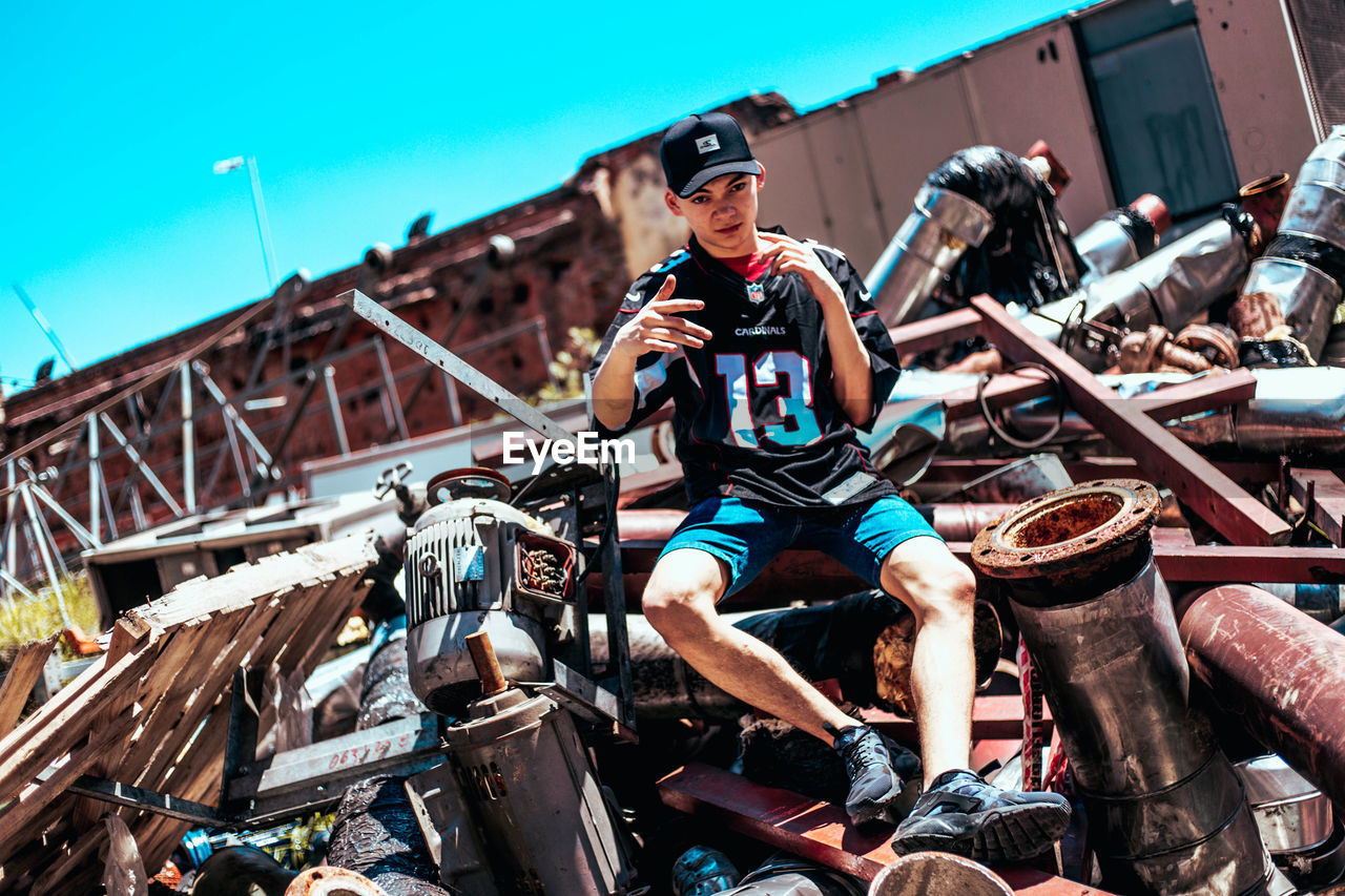 transportation, real people, mode of transportation, lifestyles, young adult, leisure activity, sitting, one person, day, land vehicle, full length, front view, nature, men, three quarter length, casual clothing, motorcycle, young women, young men, outdoors, riding